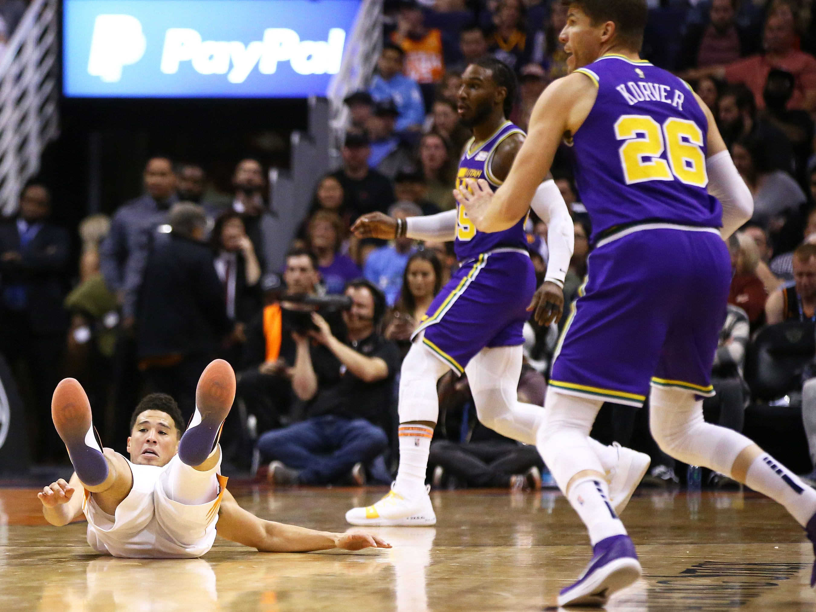 Phoenix Suns guard Devin Booker (1) falls to the court against the Utah Jazz in the second half on Mar. 13, 2019 at Talking Stick Resort Arena in Phoenix, Ariz.