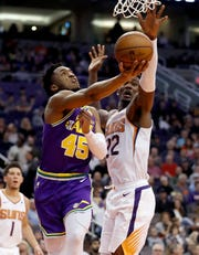 Utah Jazz guard Donovan Mitchell (45) shoots under Phoenix Suns center Deandre Ayton (22) during the first half of an NBA basketball game Wednesday, March 13, 2019, in Phoenix. (AP Photo/Matt York)