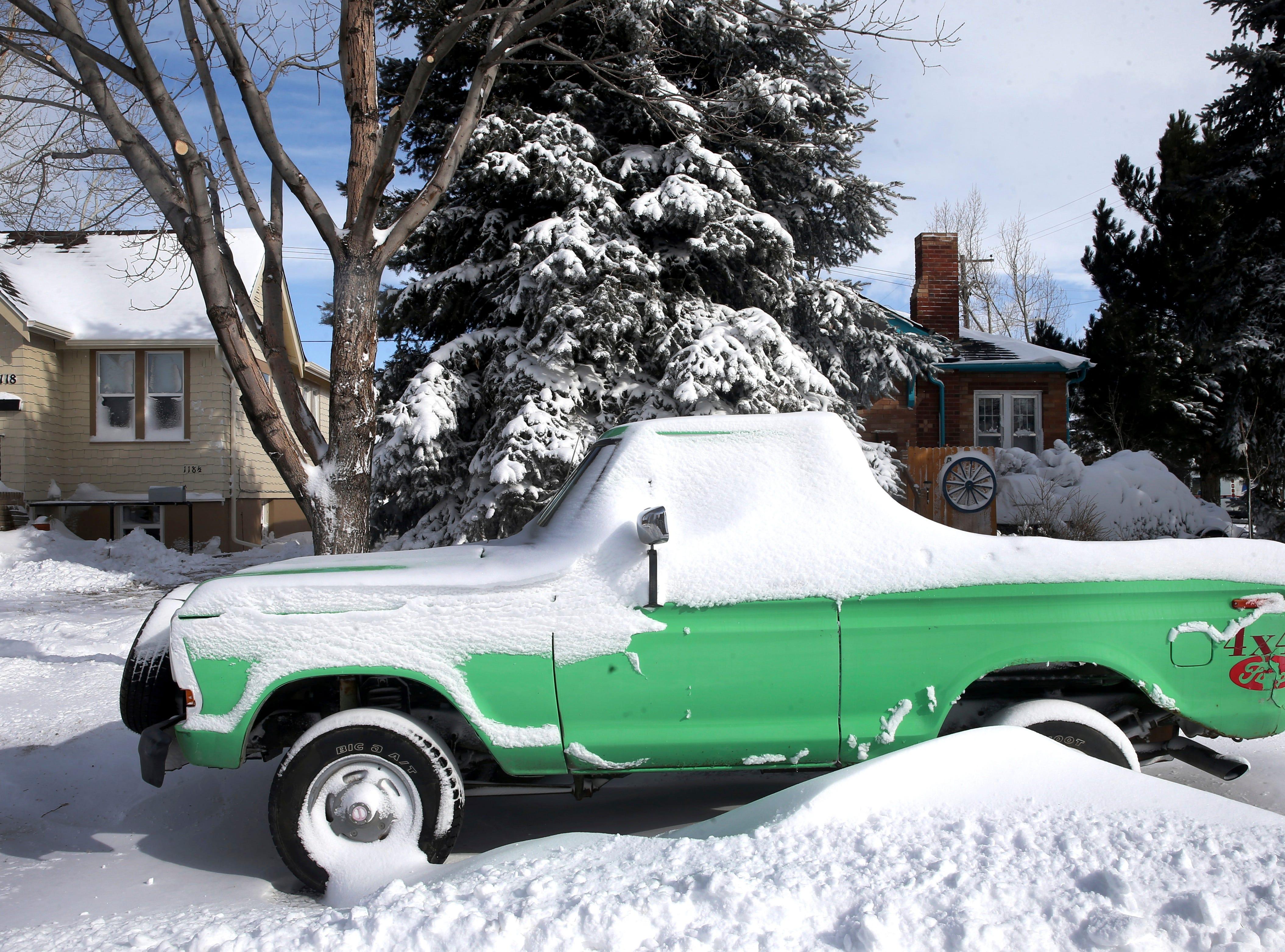 Un camión verde está cubierto de nieve en el norte de Cheyenne, Wyoming, el jueves 14 de marzo de 2019. Según el Servicio Meteorológico Nacional, 14.6 pulgadas de nieve cayeron sobre la ciudad, con velocidades máximas de viento que superan las 60 millas por hora.