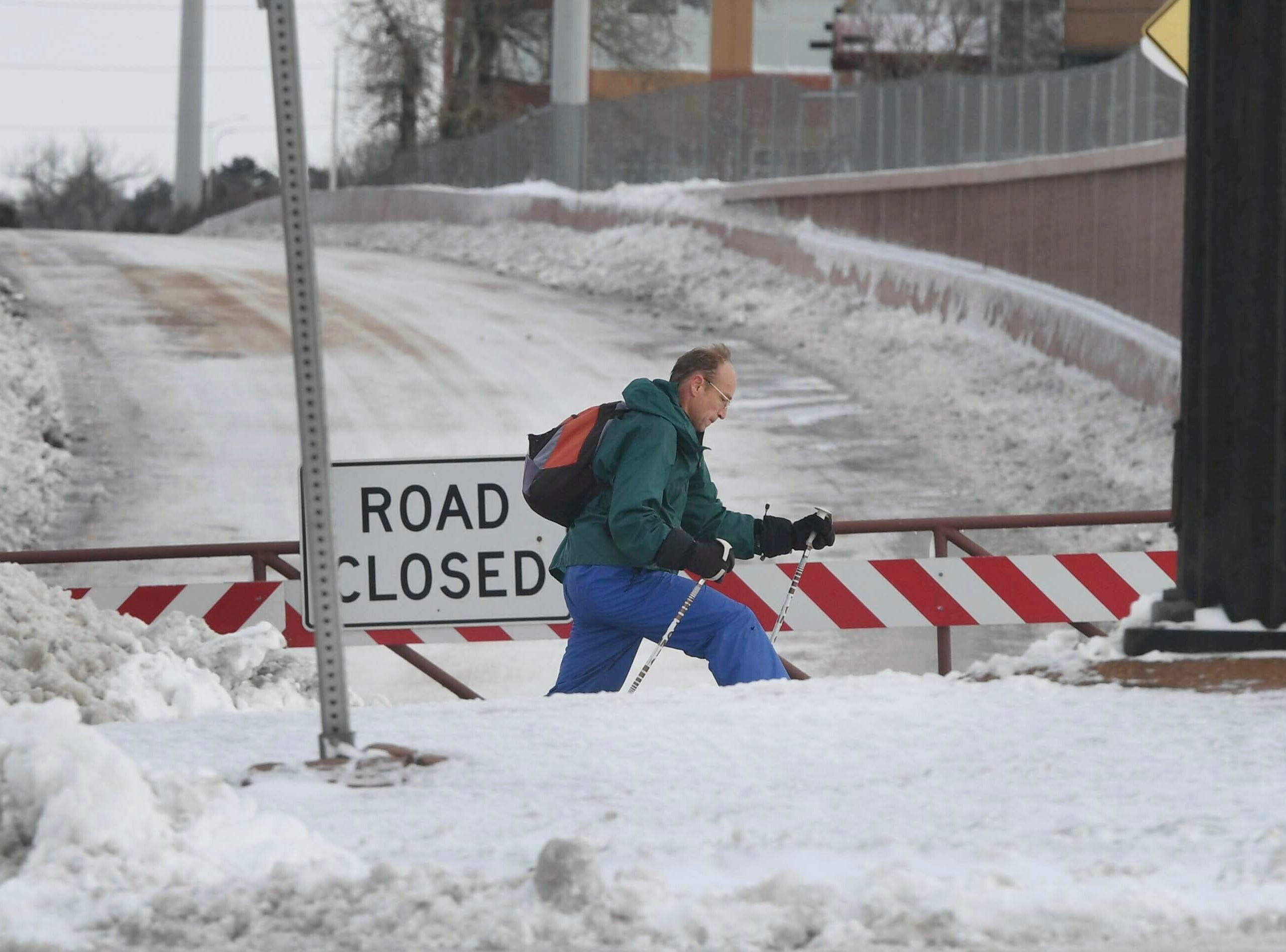 Un hombre pasa por la rampa cerrada hacia la I-25 en Woodmen Rd. en Colorado Springs, Colorado. Jueves, 14 de marzo de 2019. Una tormenta de nieve que paralizó partes de Colorado y Wyoming se precipitó hacia el Medio Oeste el jueves, lo que provocó la desaparición de las zonas blancas del oeste de Nebraska y el vertido de lluvias torrenciales que provocaron evacuaciones en las comunidades más al este.