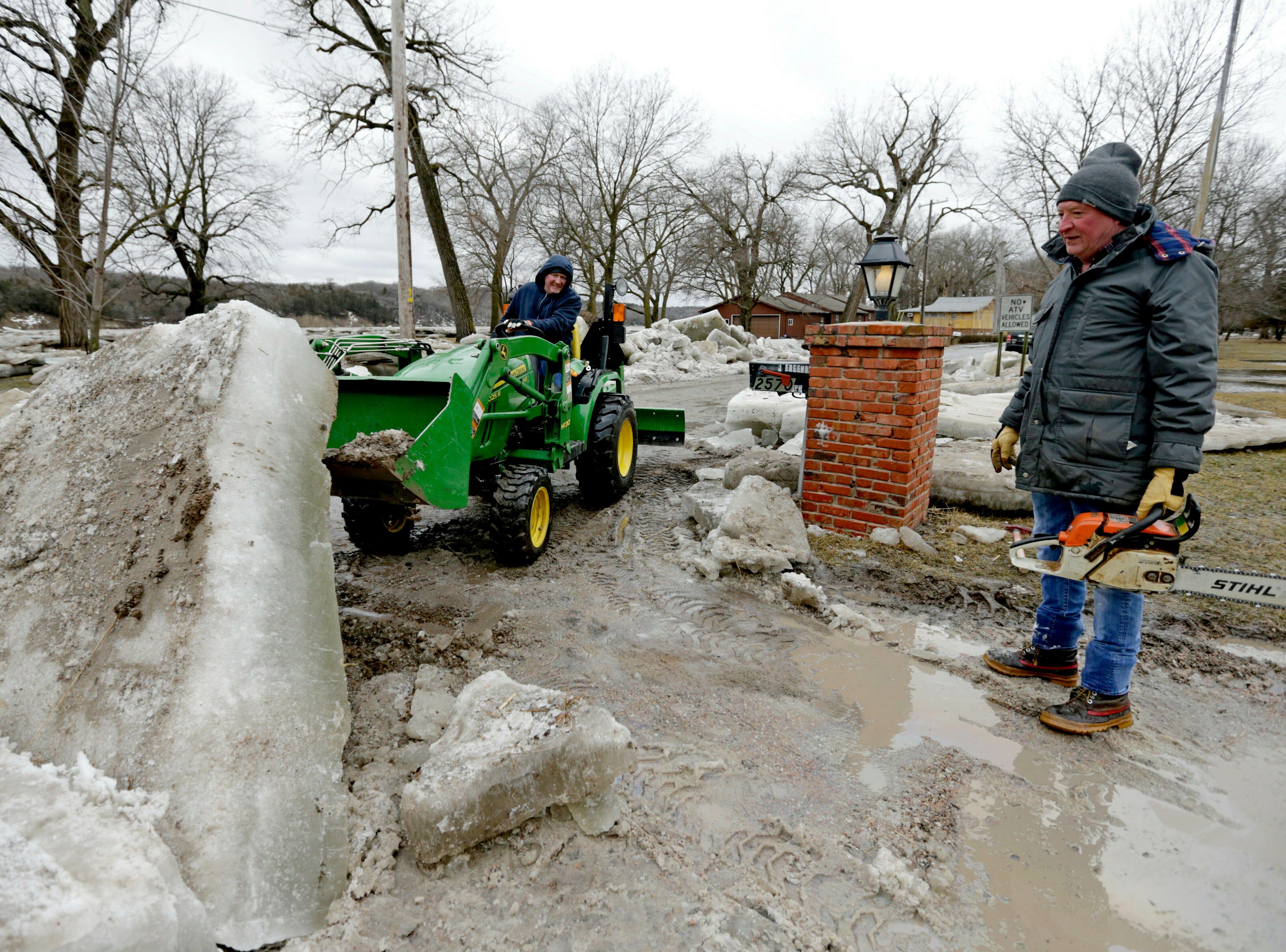 Jim Freeman (der) y su hijo Chad, trabajan para limpiar gruesos bloques de hielo de su propiedad en Fremont, Nebraska, el jueves 14 de marzo de 2019, después de que el río Platte cubierto de hielo inundara sus orillas. Se han producido evacuaciones forzadas por inundaciones en varias comunidades del este de Nebraska.