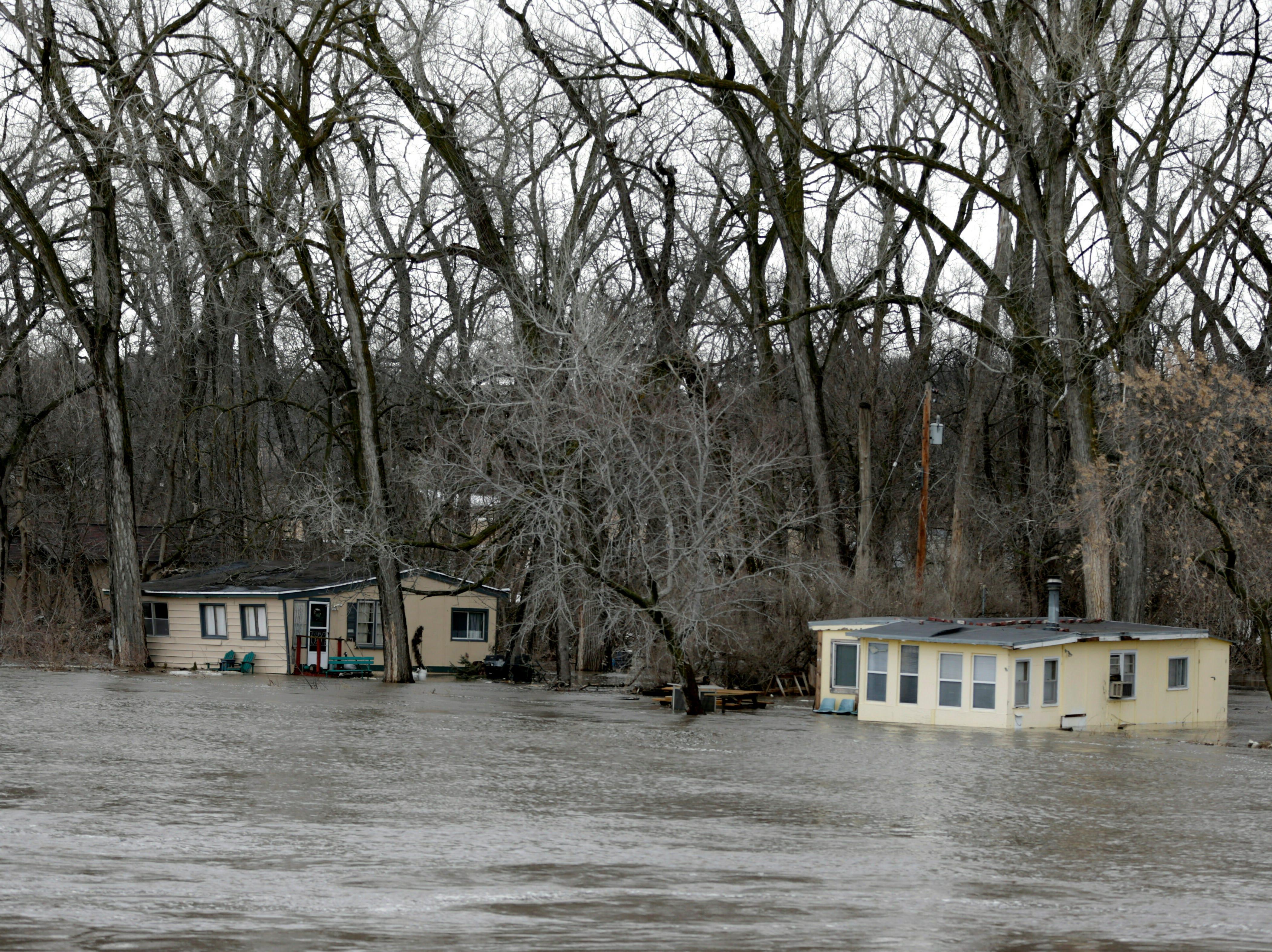 Las crecientes aguas del río Elkhorn al sur de Arlington, Nebraska, el jueves 14 de marzo de 2019, inundan las cabinas. Se han producido evacuaciones forzadas por inundaciones en varias comunidades del este de Nebraska.