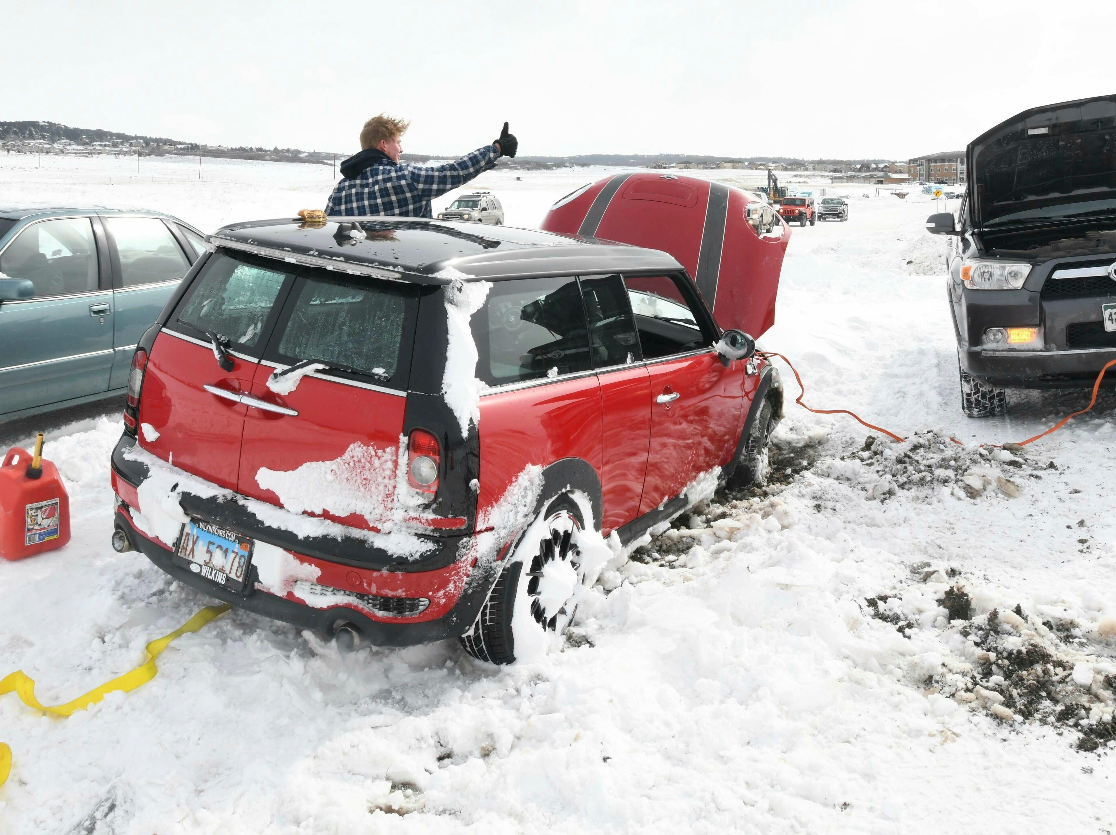 Keith Sparks le indica a su amigo, Steve Behrends, que su automóvil arrancó en una carretera exterior a la I-25 cerca de Monument, Colorado, el jueves 14 de marzo de 2019. Una tormenta de nieve que paralizó partes de Colorado y Wyoming se precipitó hacia el medio oeste el jueves, trayendo condiciones de blanqueo al oeste de Nebraska y arrojando fuertes lluvias que provocaron evacuaciones en comunidades más al este.