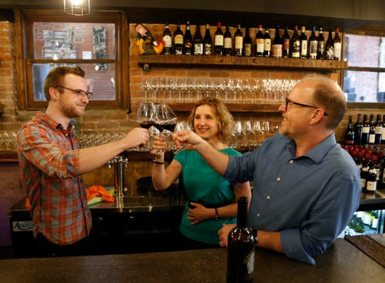 Co-owners, from left, Kai, Elke and Russell Beck toast with a bottle of Merkin Vineyards Chupacabra at 1915 Wine Cellar located at 40 Cannon Street in the City of Poughkeepsie on March 14, 2019.