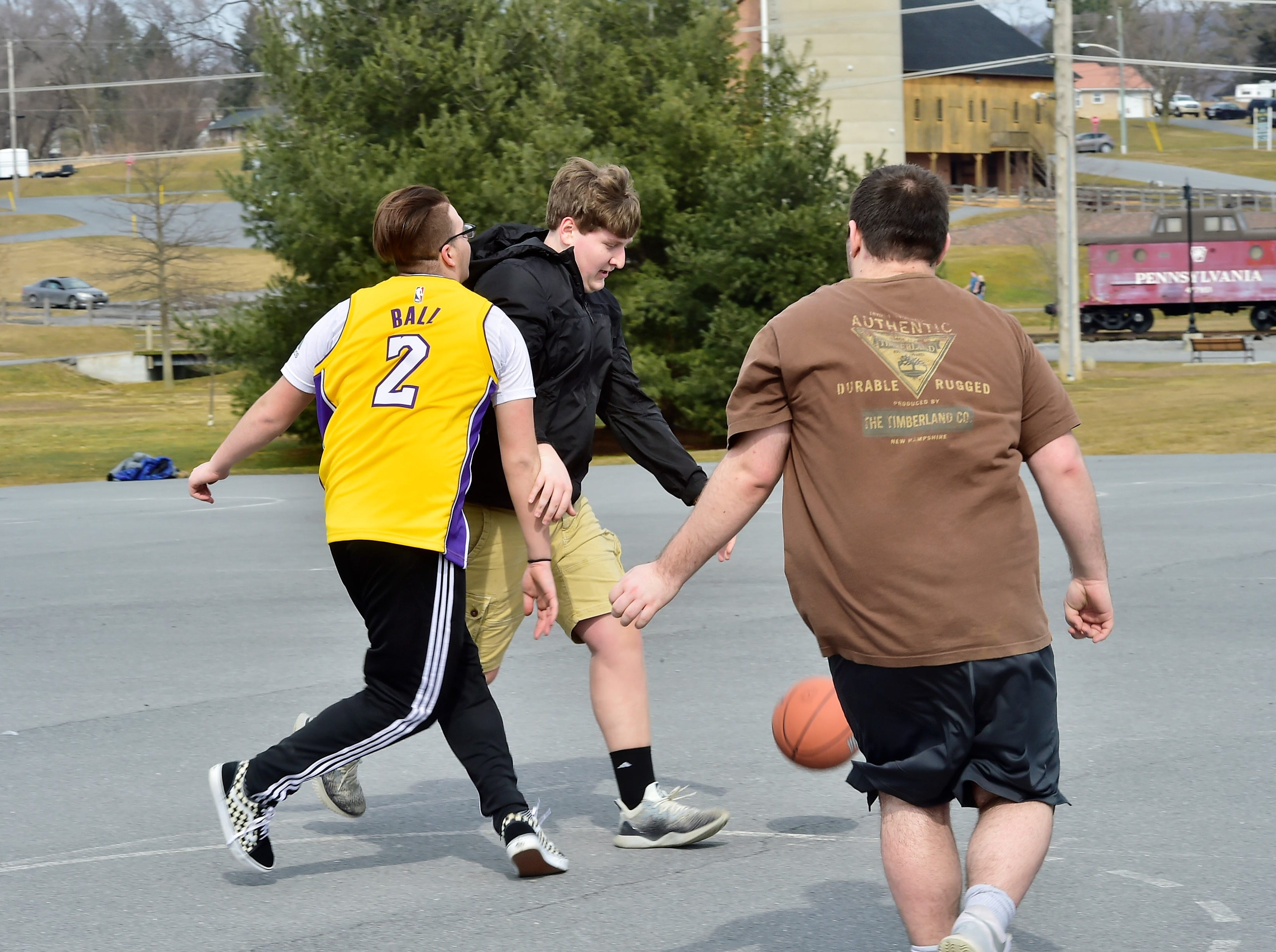 Friends from Chambersburg and Shippensburg play basketball on a warm Thursday afternoon, March 14, 2019, at Norlo Park in Fayetteville.