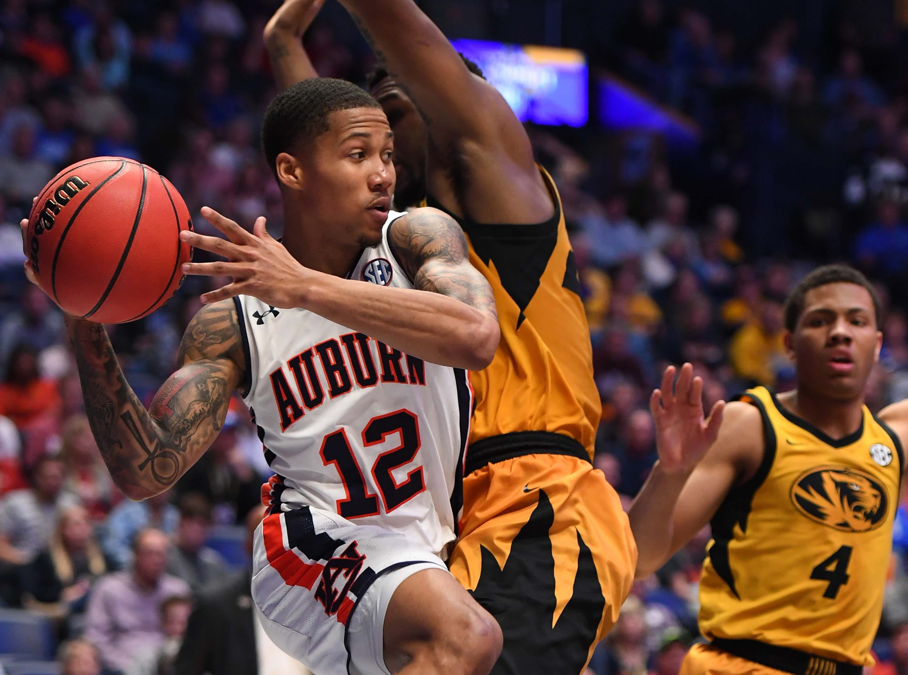Mar 14, 2019; Nashville, TN, USA; Auburn Tigers guard J'Von McCormick (12) drives baseline and looks to pass against the Missouri Tigers during the first half of the SEC conference tournament at Bridgestone Arena. Mandatory Credit: Christopher Hanewinckel-USA TODAY Sports