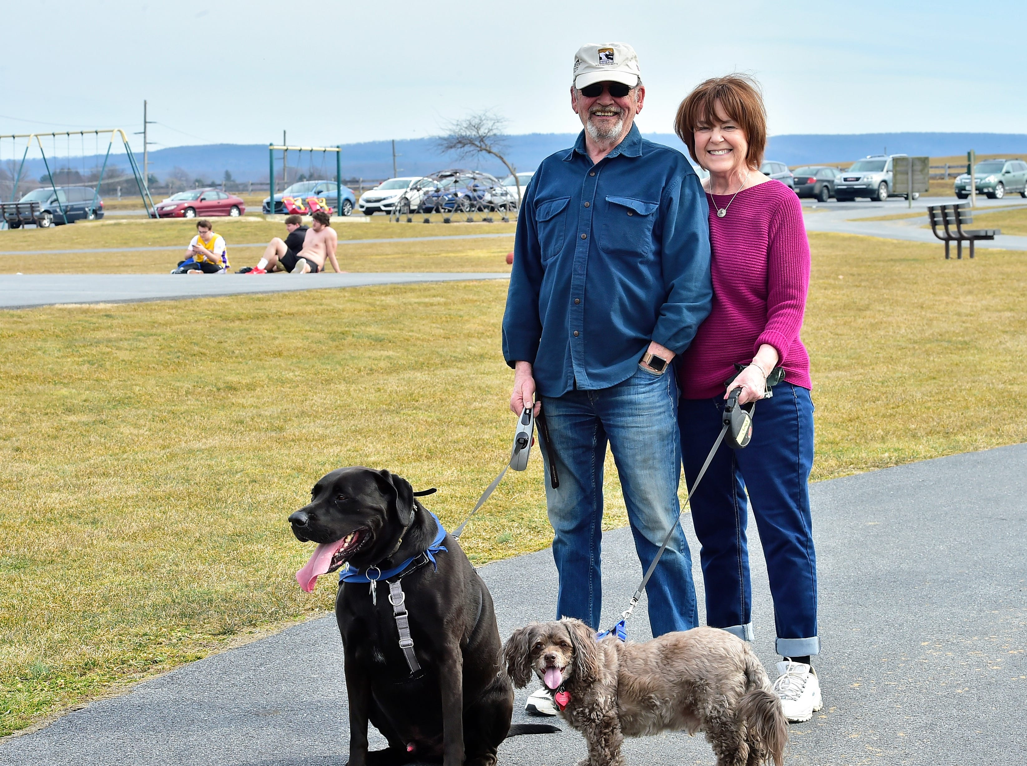 Ron Thompson, Fayetteville, and Maxine Porcelli, Chambersburg, walk their dogs on a warm Thursday afternoon, March 14, 2019, at Norlo Park in Fayetteville.