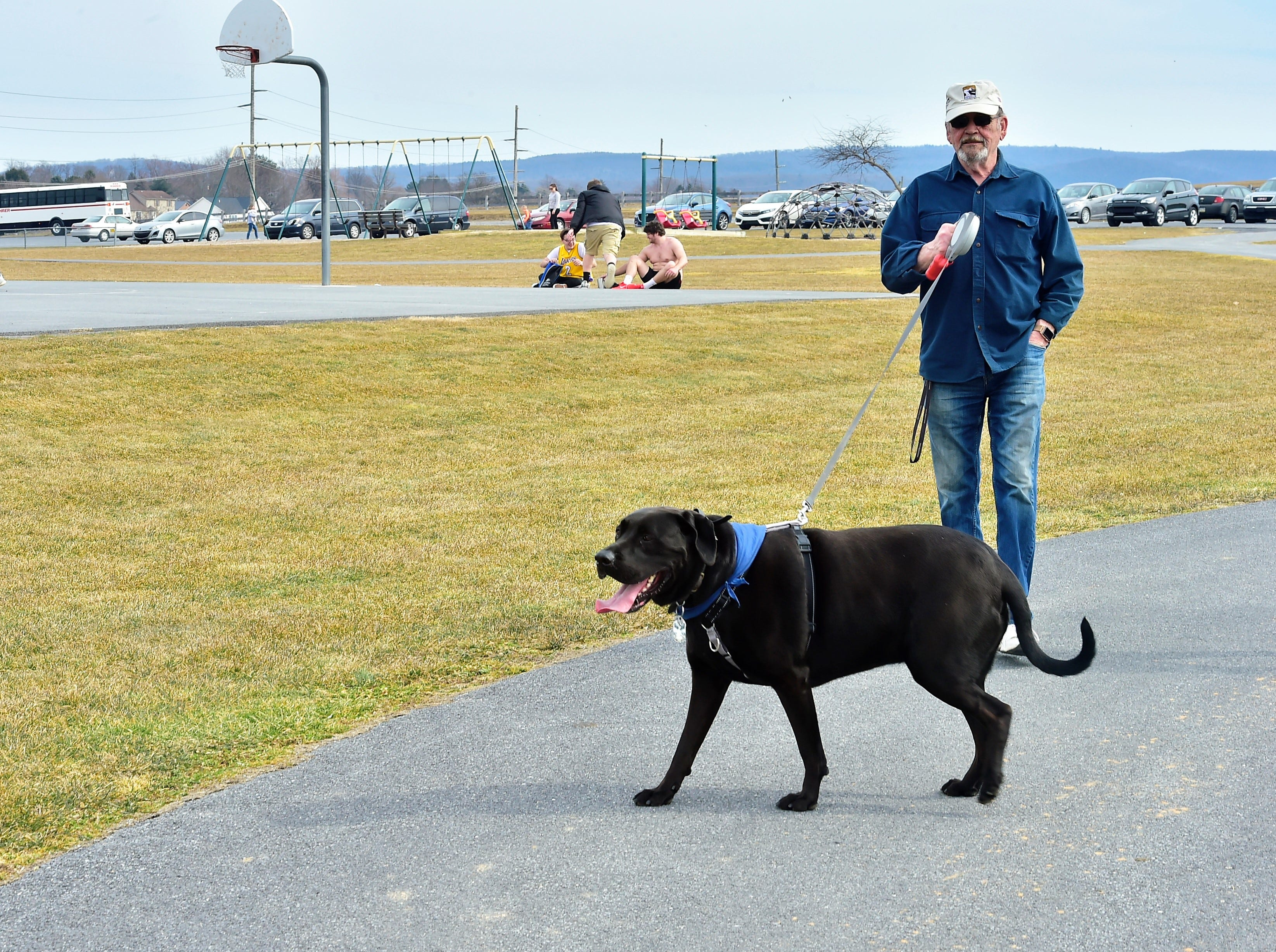 Ron Thompson, Fayetteville, walks his dog on a warm Thursday afternoon, March 14, 2019, at Norlo Park in Fayetteville.