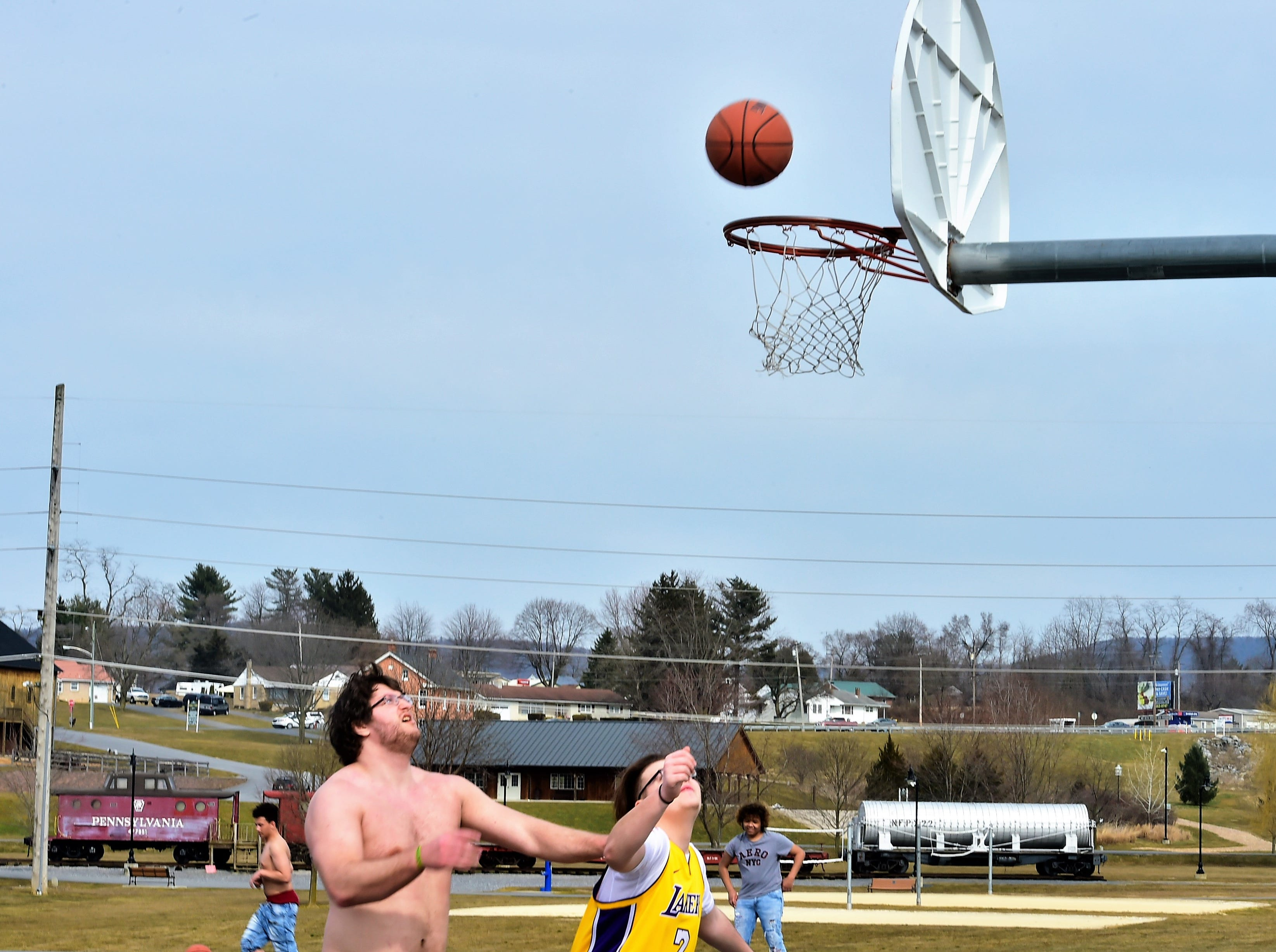 Friends from Shippensburg and Chambersburg play basketball on a warm Thursday afternoon, March 14, 2019, at Norlo Park in Fayetteville.