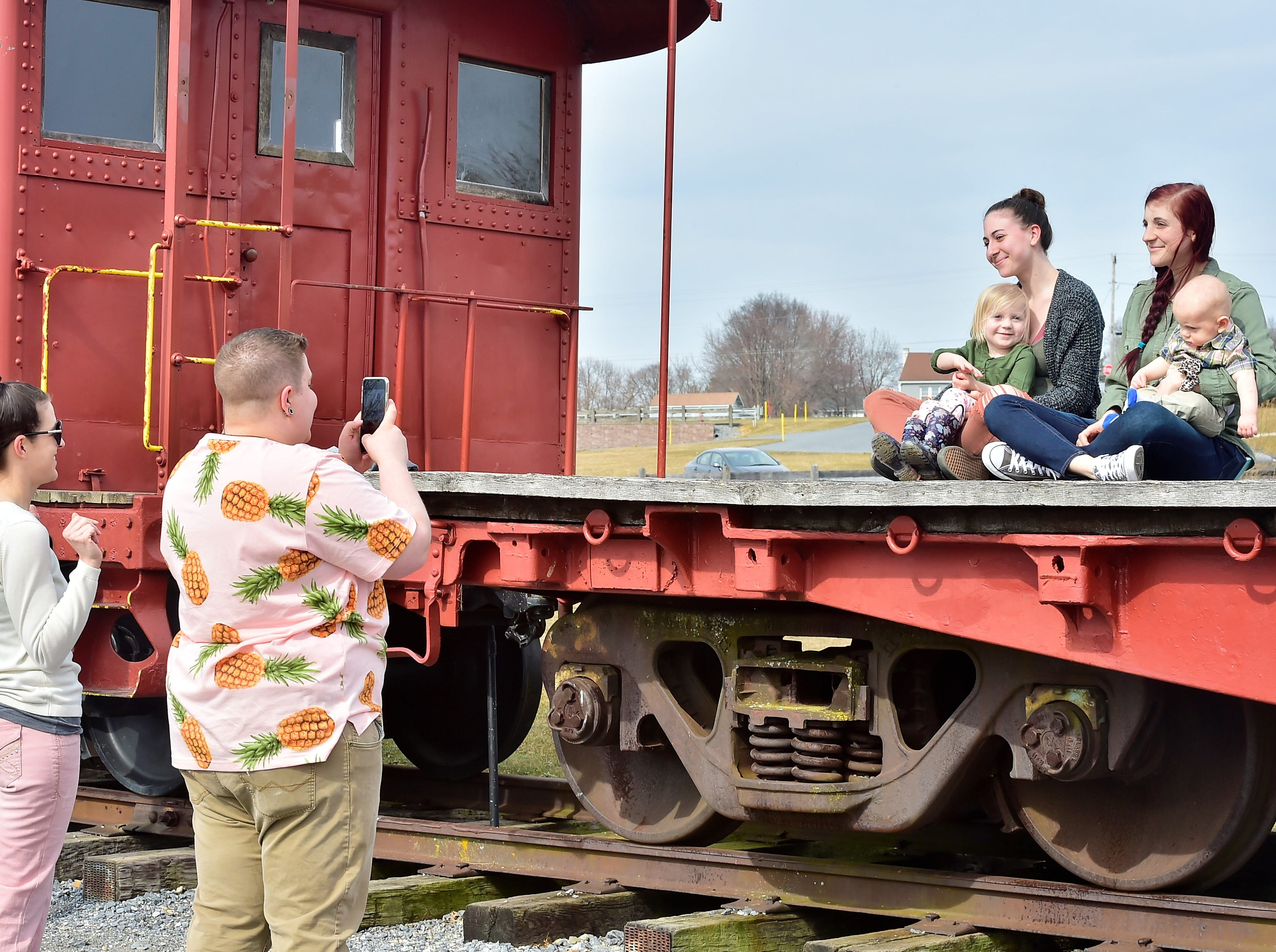 A group of friends take photos at one of the railroad cars at Norlo Park in Fayetteville on Thursday afternoon, March 14, 2019. Pictured are, from left: Krista Heinbaugh, Chambersburg; Taryn Leas, Shippensburg; Addison Chapman, 3; Samantha Laughman, Shippensburg; Christy Chapman of Jacksonville, N.C.; and Jamison Chapman, 8 months.