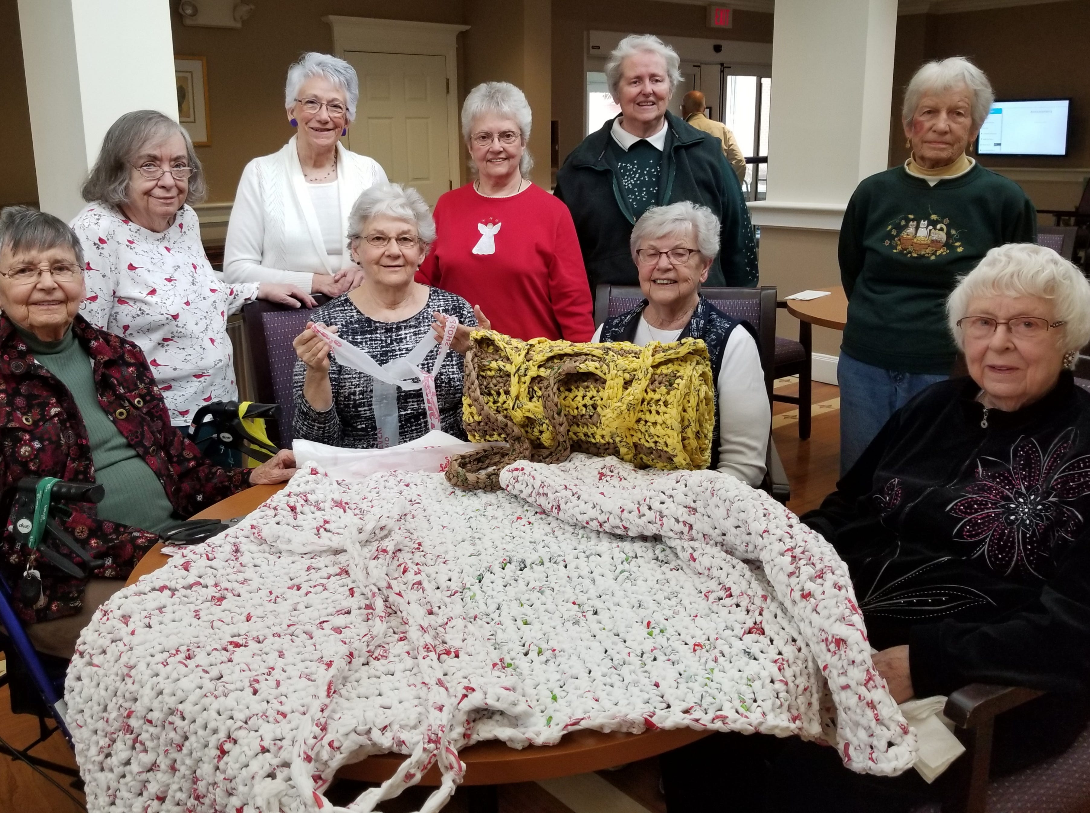 Normandie Ridge residents, from left, Elizabeth Petrick, Joyce Brown, Virginia Foor, Fran Wyre, Betty Shive, Vickie Eisenhart, Karen Naumann, Fern Shanabrook, Ruth Carrozza pose with sleeping mats which they made from recycled plastic bags. ÒThe Plarn People of Normandie RidgeÓ have been making the mats from recycled plastic bags. The mats will be donated to LifePath Christian Ministries in York, a non-profit agency helping the homeless and those living in poverty. submitted