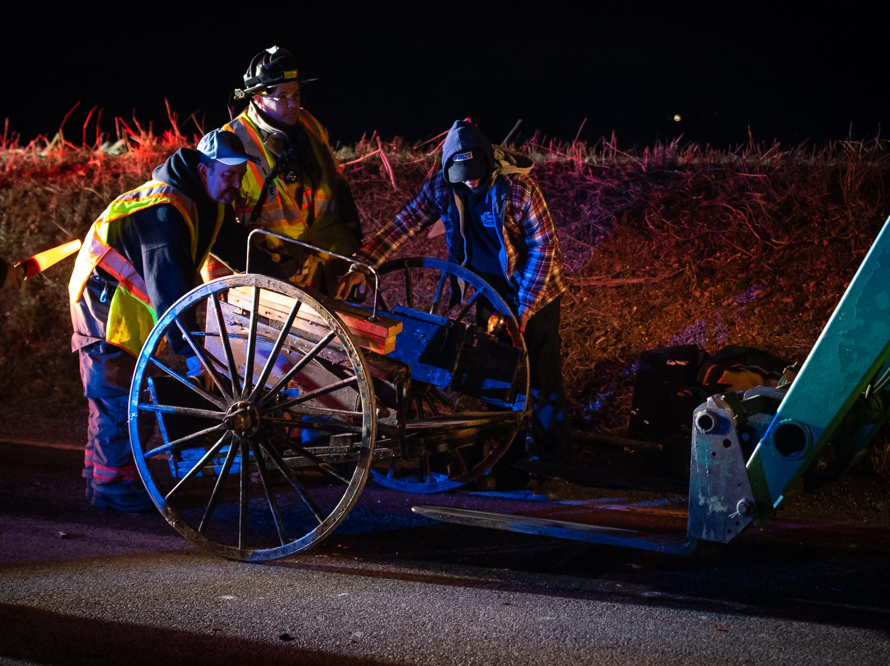 Firefighters help several people load a horse and buggy onto the forklift of a tractor at the scene of a vehicle vs a horse and buggy on the 3400 block of Jefferson Road , Wednesday, March 13, 2019, in Codorus Township. According to fire officials, there were no major injuries to people or the horse involved, which was caught after it ran from the accident.