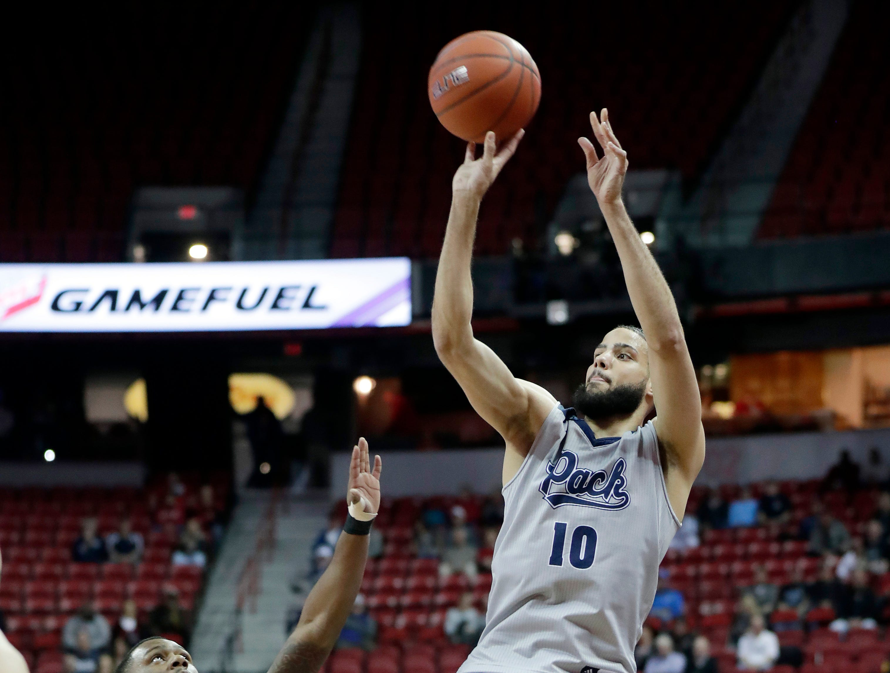 Nevada's Caleb Martin (10) shoots as Boise State's Marcus Dickinson defends during the first half of an NCAA college basketball game in the Mountain West Conference men's tournament Thursday, March 14, 2019, in Las Vegas. (AP Photo/Isaac Brekken)