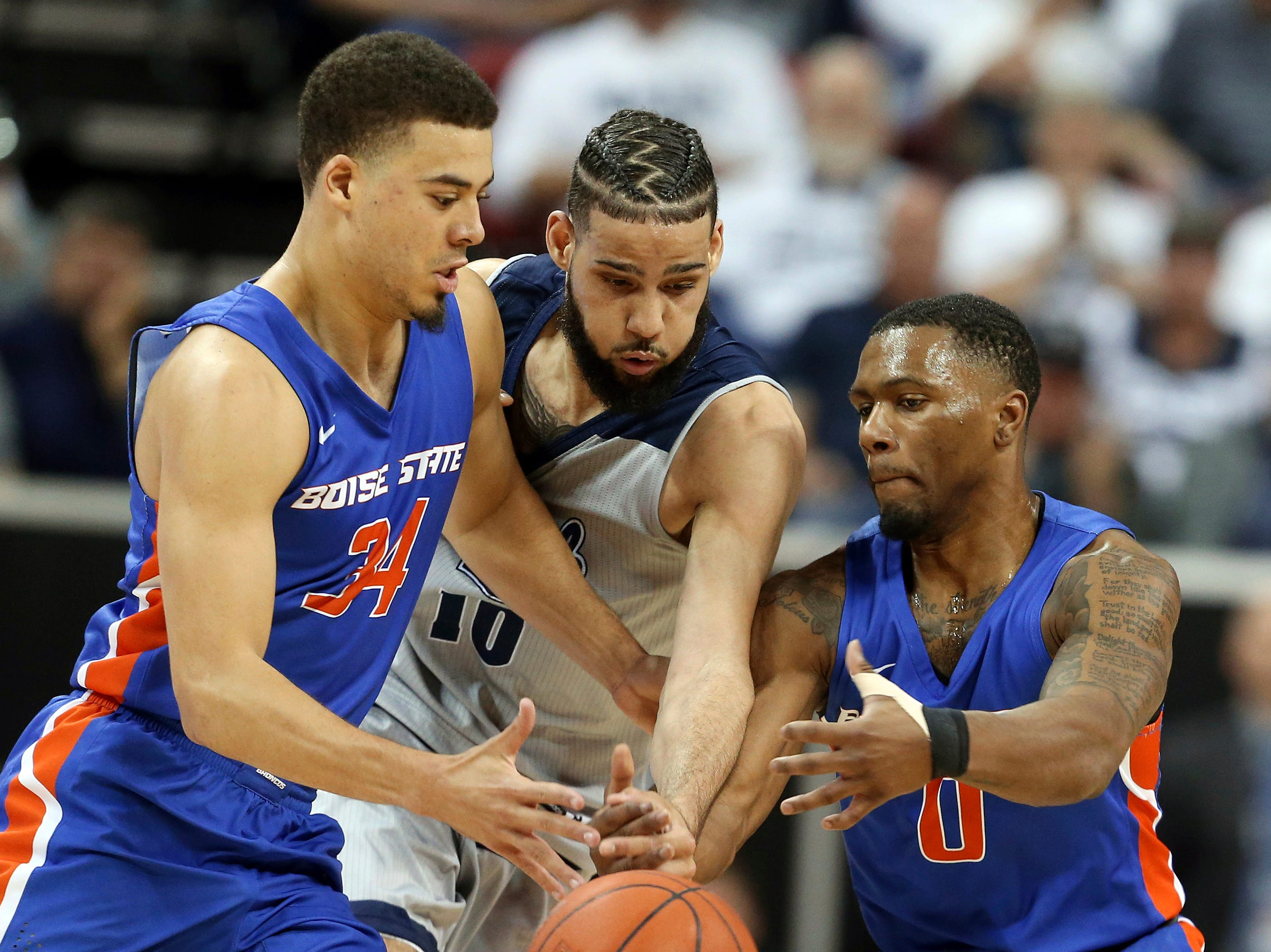 Boise State's Alex Hobbs (34) and Marcus Dickinson (0) reach for a loose ball with Nevada's Caleb Martin (10) during the first half of an NCAA college basketball game in the Mountain West Conference men's tournament Thursday, March 14, 2019, in Las Vegas. (AP Photo/Isaac Brekken)