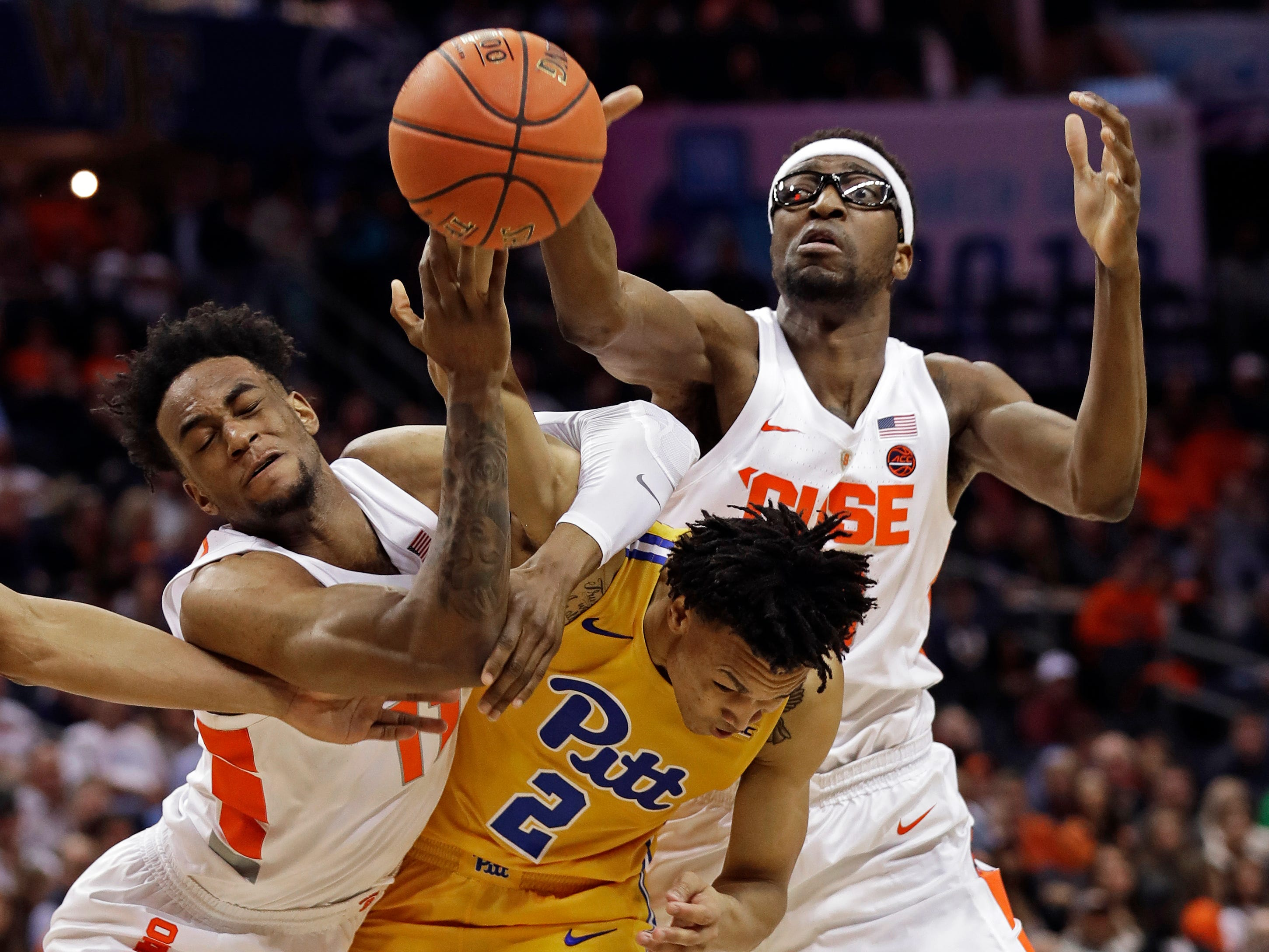 Pittsburgh's Trey McGowens (2) battles Syracuse's Paschal Chukwu, right, and Oshae Brissett, left, for a rebound during the first half of an NCAA college basketball game in the Atlantic Coast Conference tournament in Charlotte, N.C., Wednesday, March 13, 2019.
