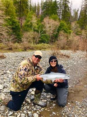 Dave Jacobs of Professional Guide Service (left) and Laura Curiel from Corning (right) hold one of her many beautiful steelhead hooked this week on southern Oregon's Chetco River.