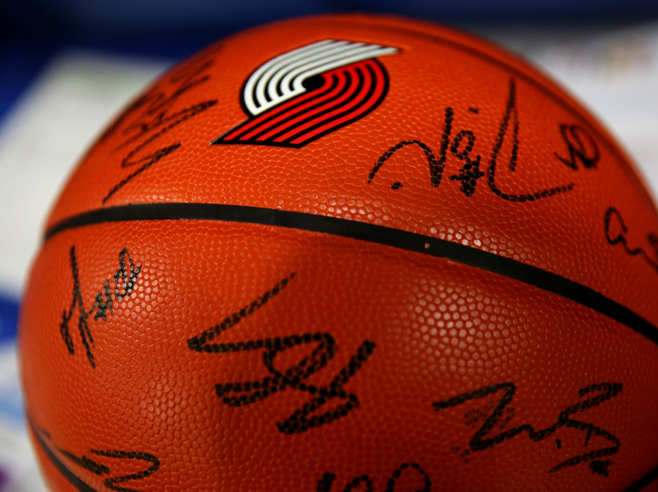A basketball autographed by Blazers players is ready to be auctioned off during a break in the second annual House vs. Senate charity basketball tournament at the Boys & Girls Club in Salem on March 13, 2019. The tournament raised more than $10,000 for the Oregon Alliance of Boys & Girls Clubs.
