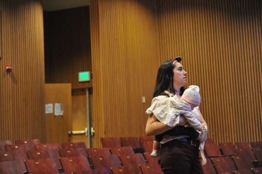 "Holding her seven-month-old daughter Luna, Emily Morales, founder and artistic director of Artists Ink, watches as actors rehearse ""ReAlisal: Stories from East Alisal"" Wednesday night."