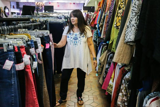 Marie Aguirre organizes clothes Thursday, March 14, 2019, at A Second Look Consignment.