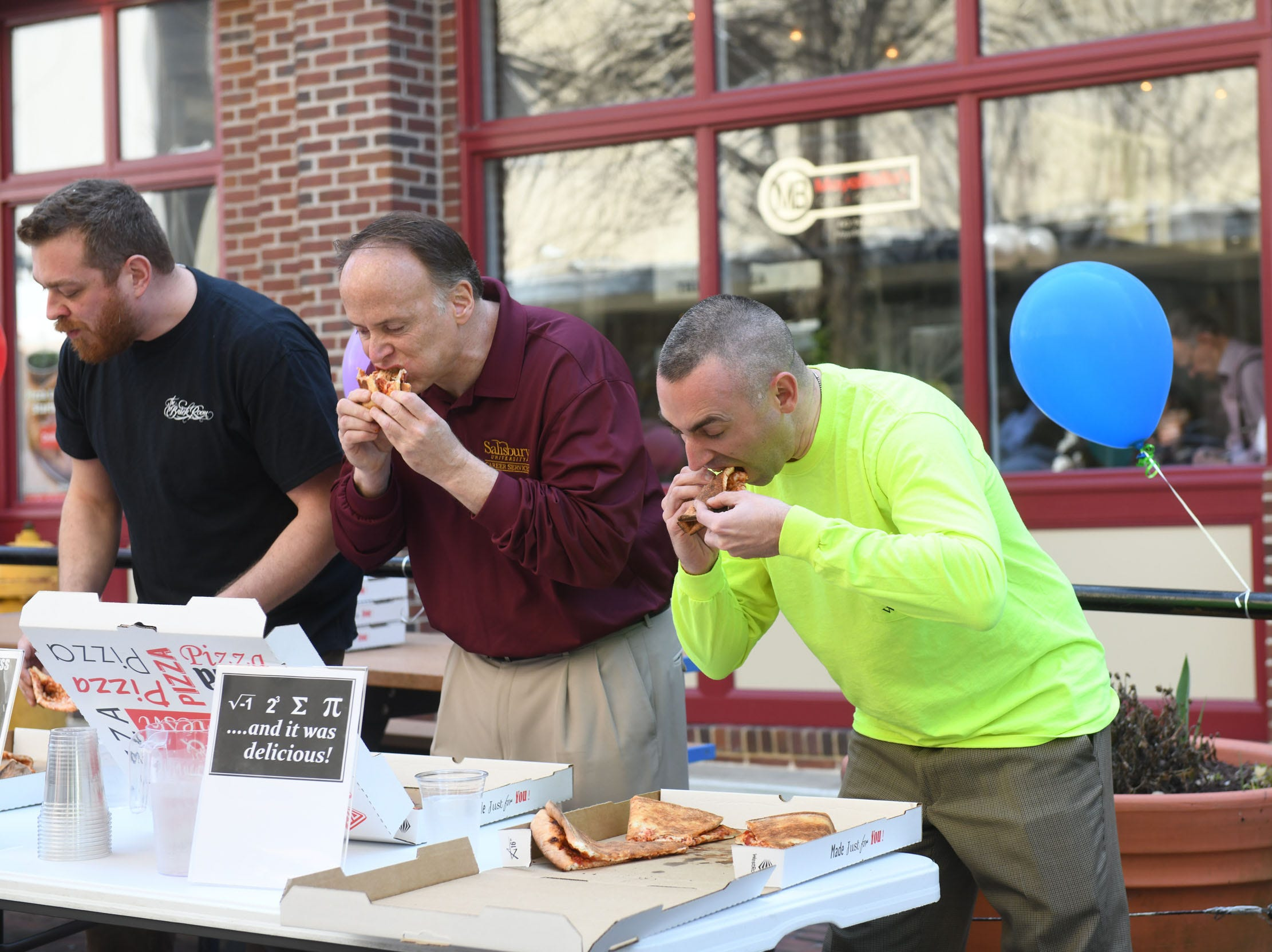 (Right) Mayor Jake Day works on eating a 16-inch pie during PI(e) Day in Downtown Salisbury on Thursday, March 14, 2019.