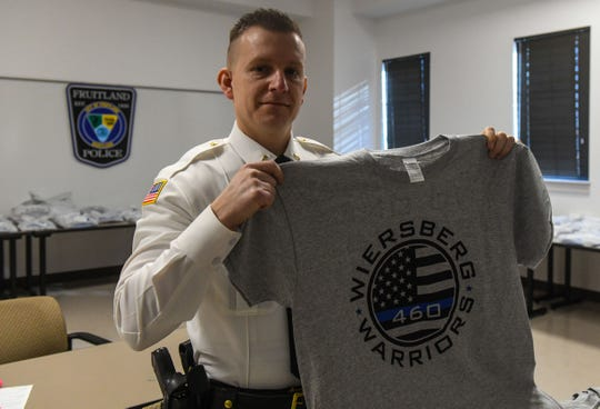 The Fruitland Police Department Lt. Dan Holland holds the t-shirt that they are selling to raise money to help fellow Officer Spencer Wiersberg's battle against cancer. Thursday, March 14, 2019.