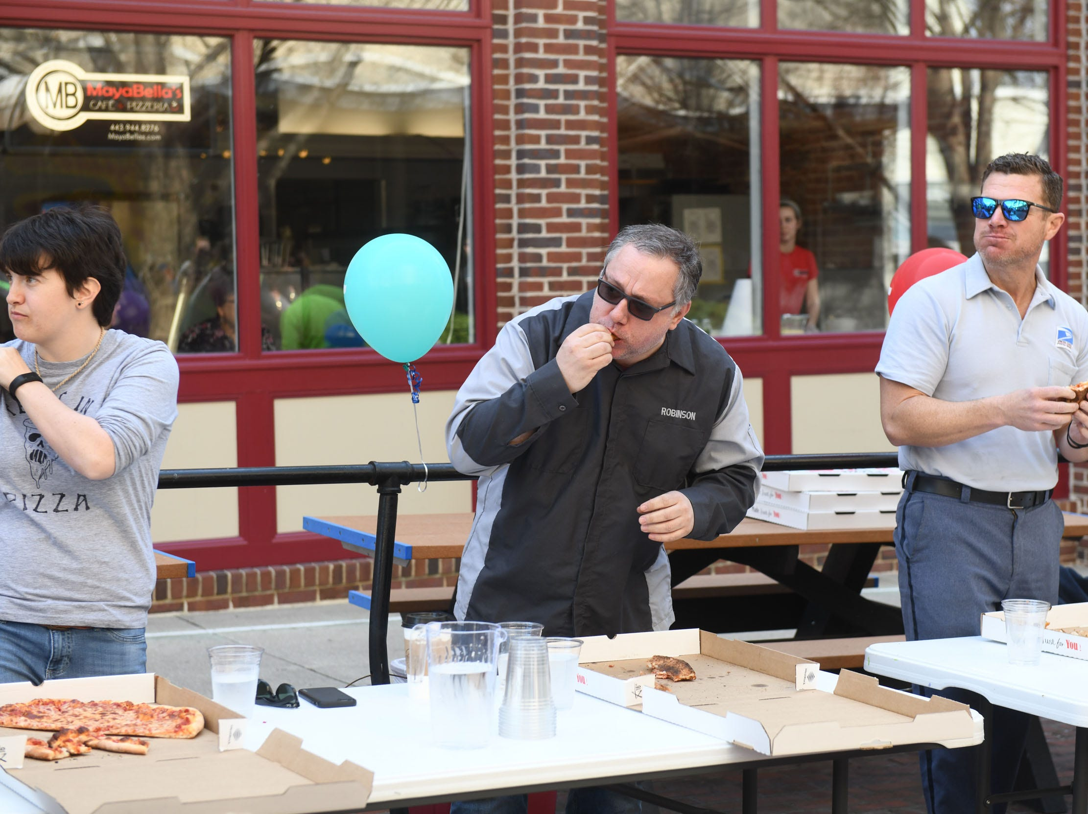 (Middle) John Robinson works on eating a 16-inch pie during PI(e) Day in Downtown Salisbury on Thursday, March 14, 2019.