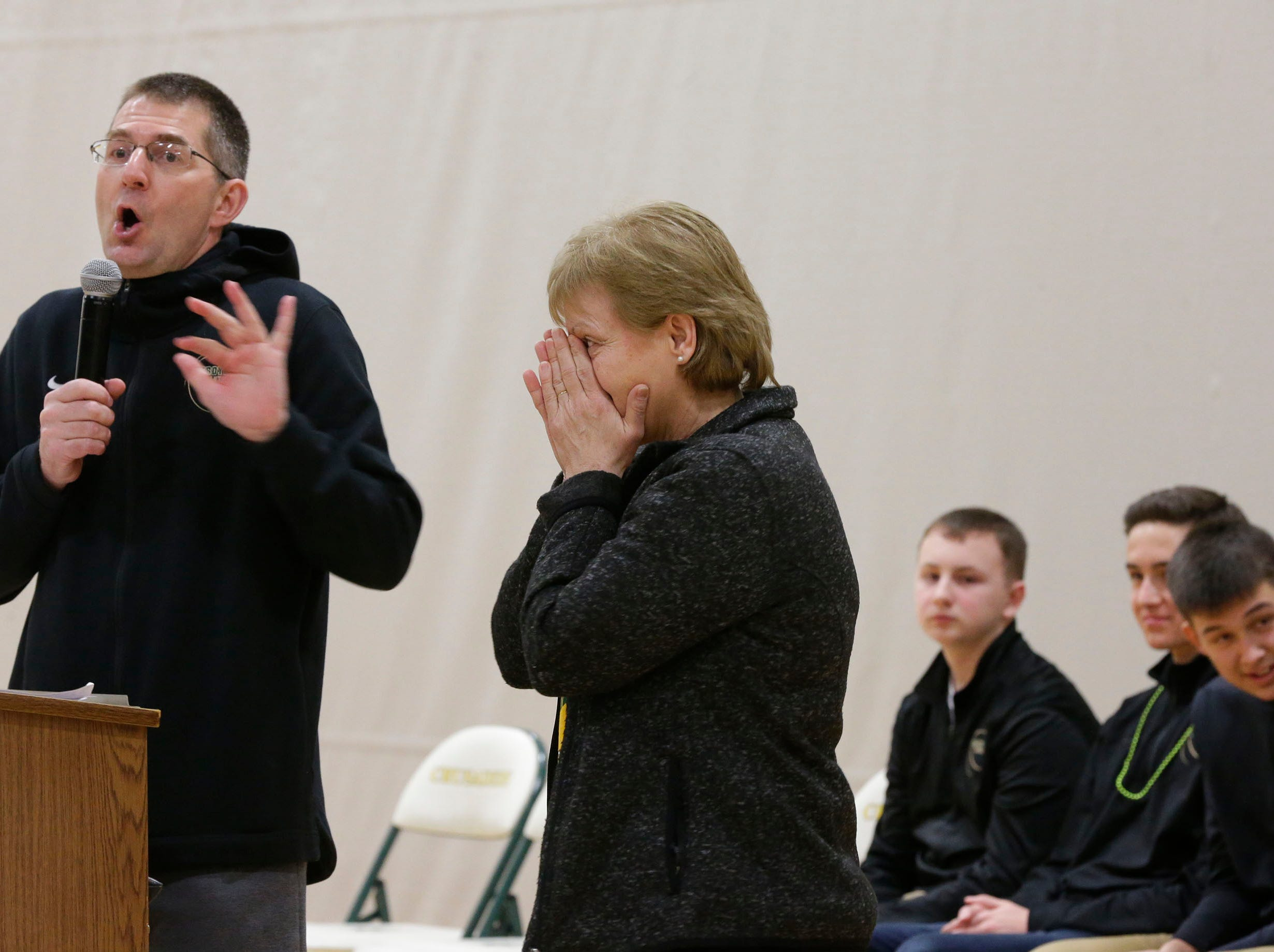 Sheboygan Lutheran teach Jeff Jurss reacts to teacher Julie Reseburg try to recite the names of the players on the team during a send off rally to Madison for WIAA state basketball tournaments, Thursday, March 14, 2109, in Sheboygan, Wis.