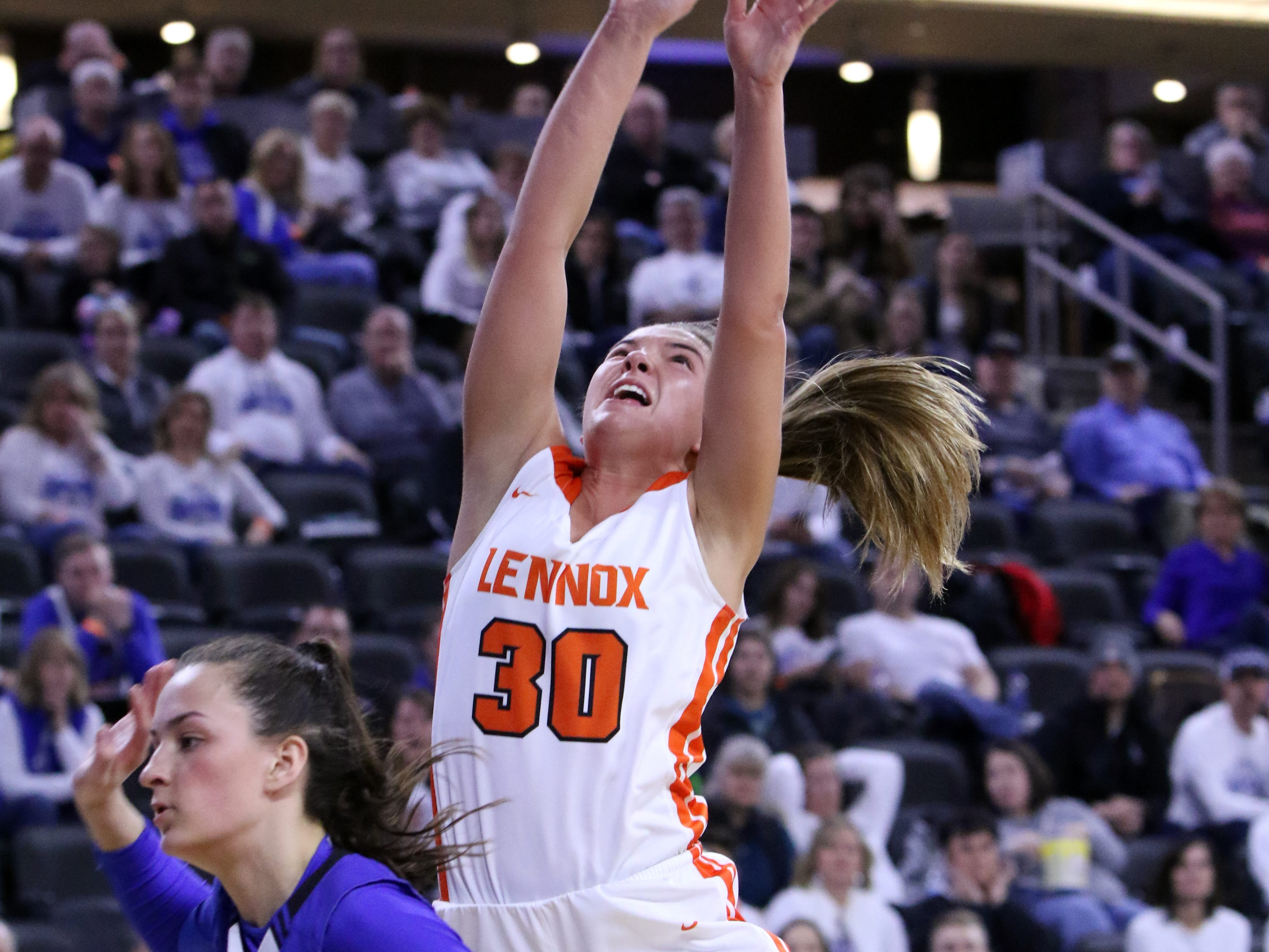 Rianna Fillipi of Lennox is fouled as she gets off a shot by Ciara Benson of St Thomas More during Thursday's game at the Premier Center in Sioux Falls.