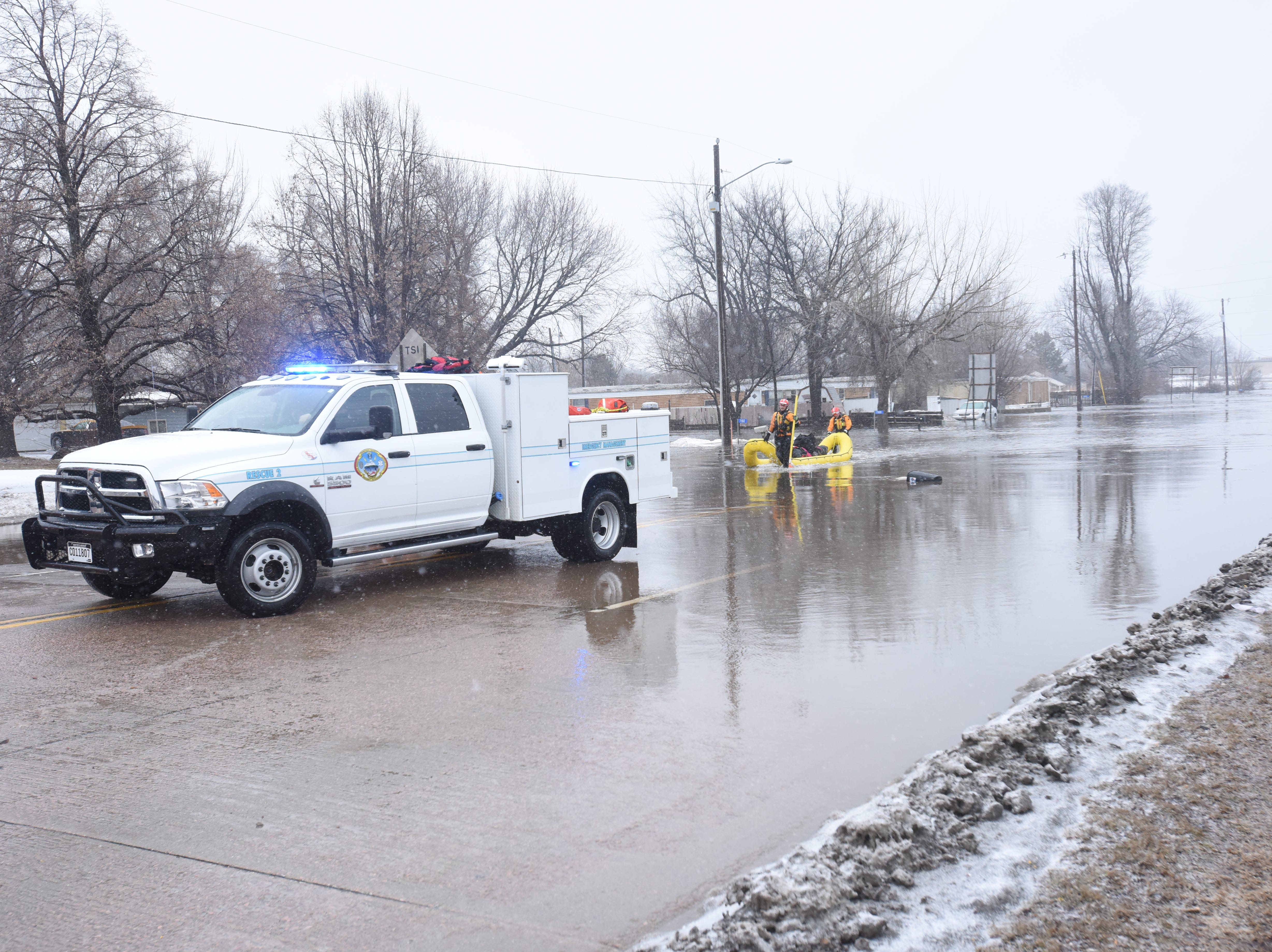 Minnehaha County Emergency Management, Sheriff's Office, Sioux Falls Fire Rescue, Hartford Fire and Paramedics Plus help evacuate people from their homes on W 12th St. across from Legacy Park Thursday, March 14, after roads flooded across the county.
