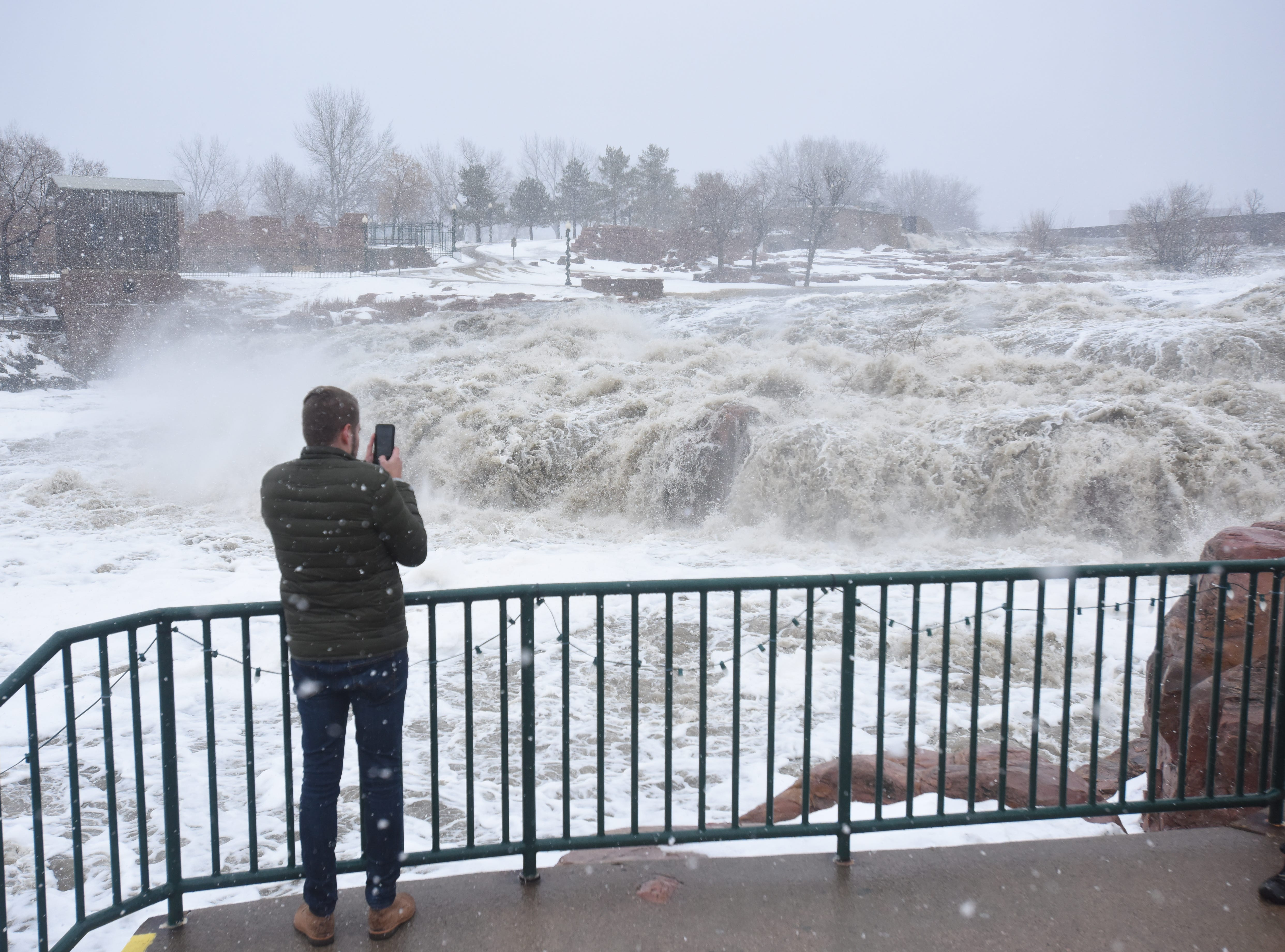 Thomas Christiansen takes a photo of Falls Park Thursday, March 14, 2019, after rain caused flooding all around Sioux Falls.