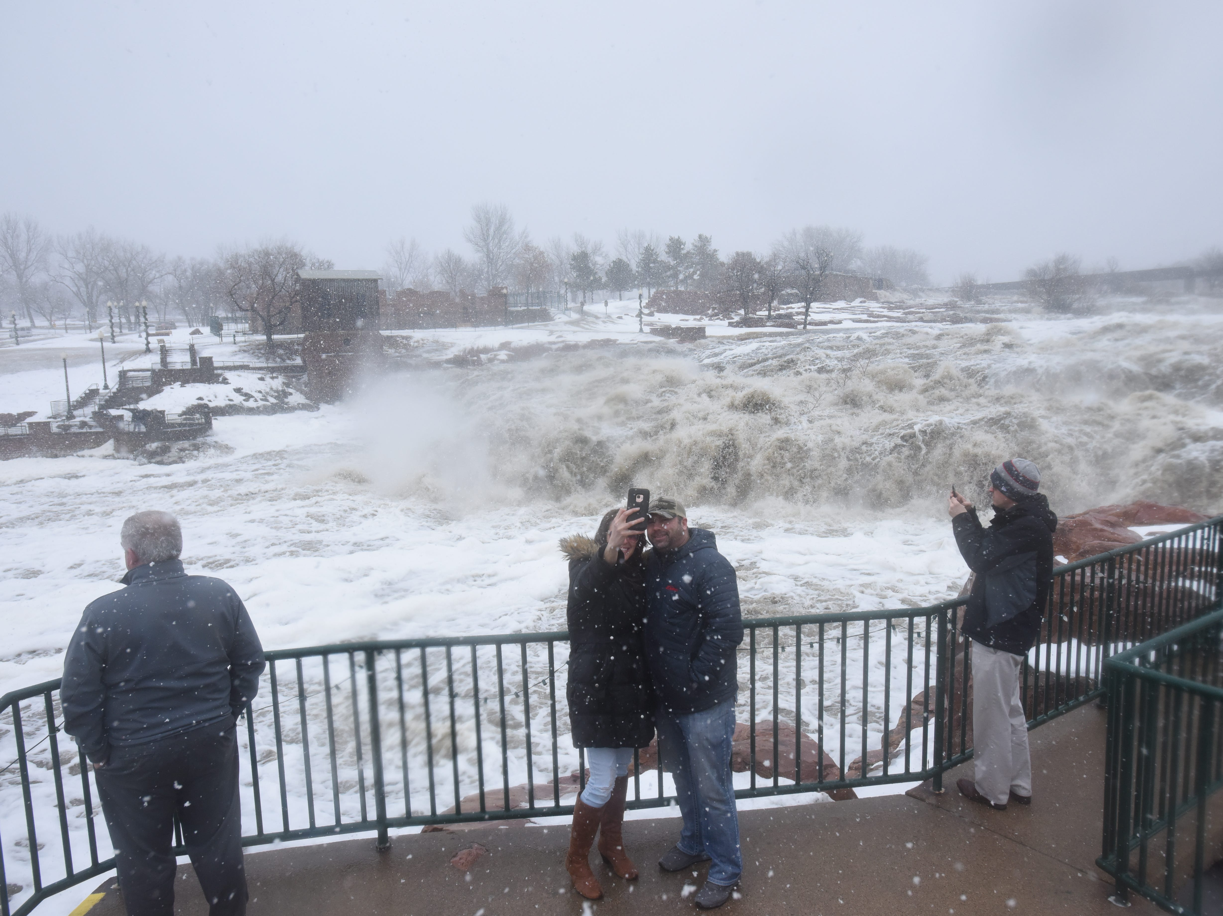 Vanessa Thaler and Shawn Rohrich pose for a photo in front of the rushing falls at Falls Park Thursday, March 14, as waters flooded roads all around Sioux Falls.