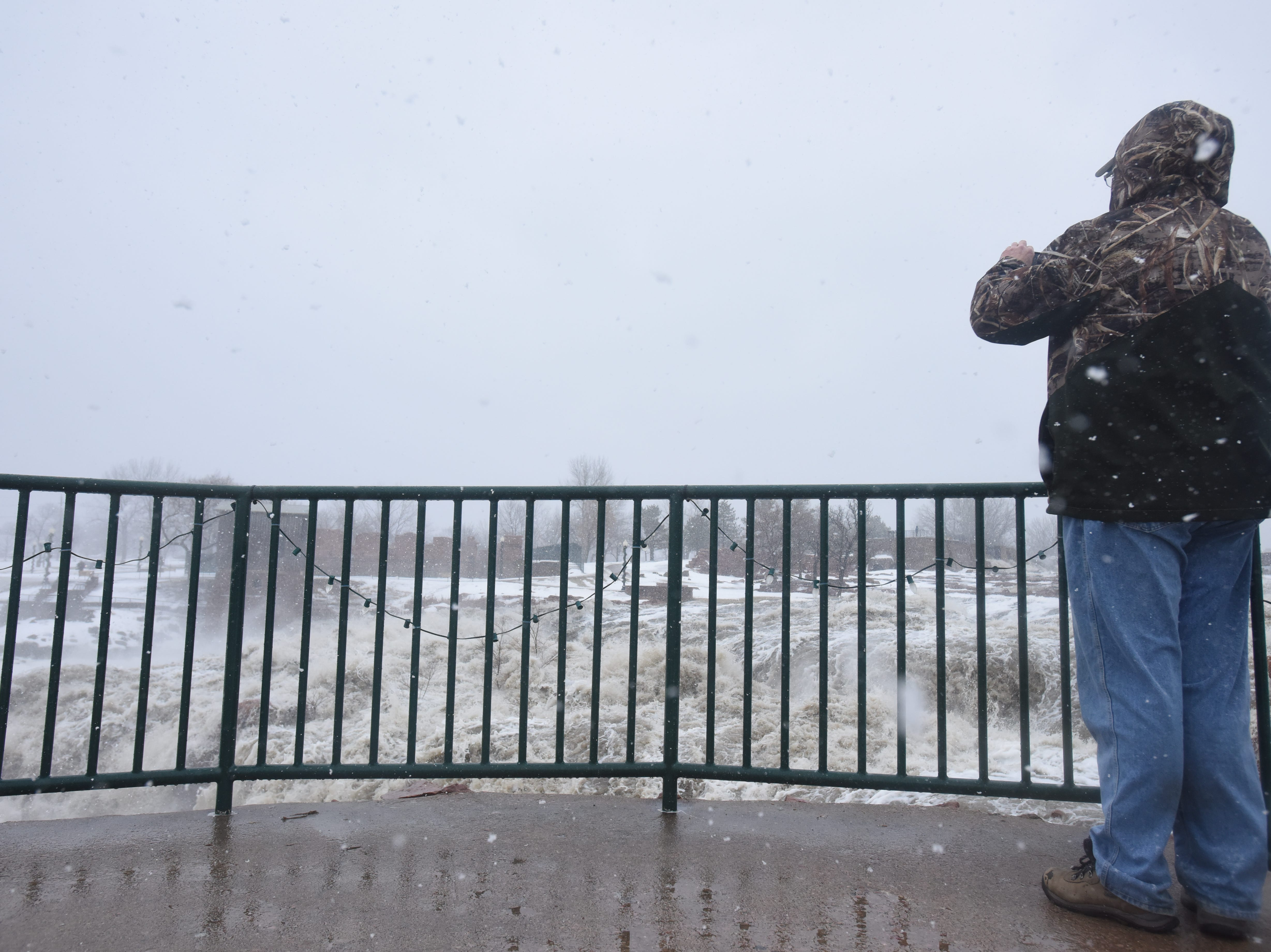 Don Thorpe, of Mount Vernon, takes a photo of Falls Park Thursday, March 14, 2019, after rain caused flooding all around Sioux Falls.