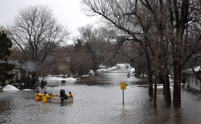 Sioux Falls Fire Rescue crews take a boat to check for residents in houses that were flooded in the area of Minnesota Avenue and Lotta Street.