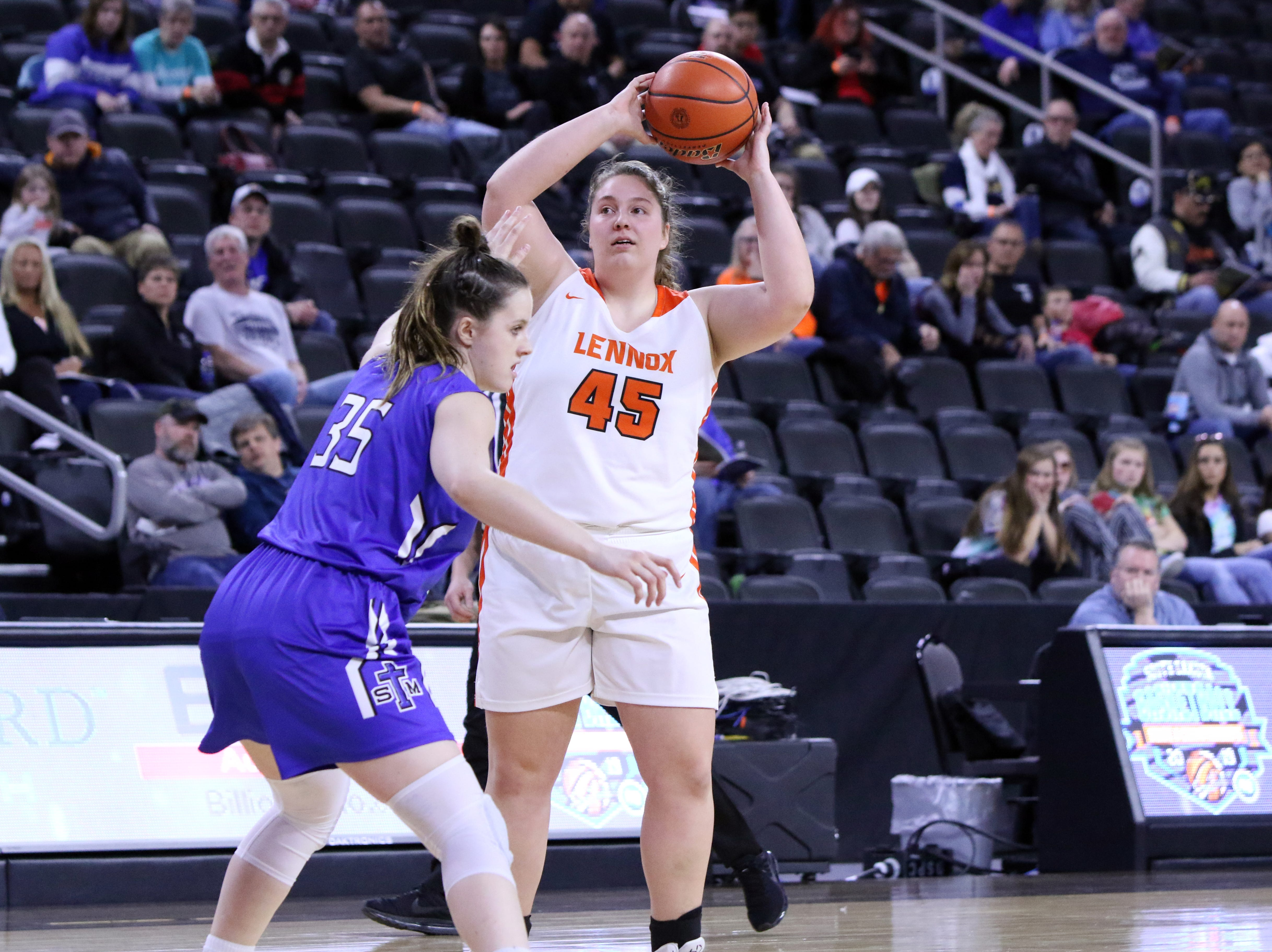 Leslie Fillipi of Lennox looks to pass the ball as Lizzy Elder of St Thomas More defends during Thursday's game at the Premier Center in Sioux Falls.