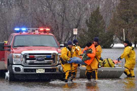Sioux Falls Fire Rescue crews take a woman to safety after residences were flooded in the area of Minnesota Avenue and Lotta Street.