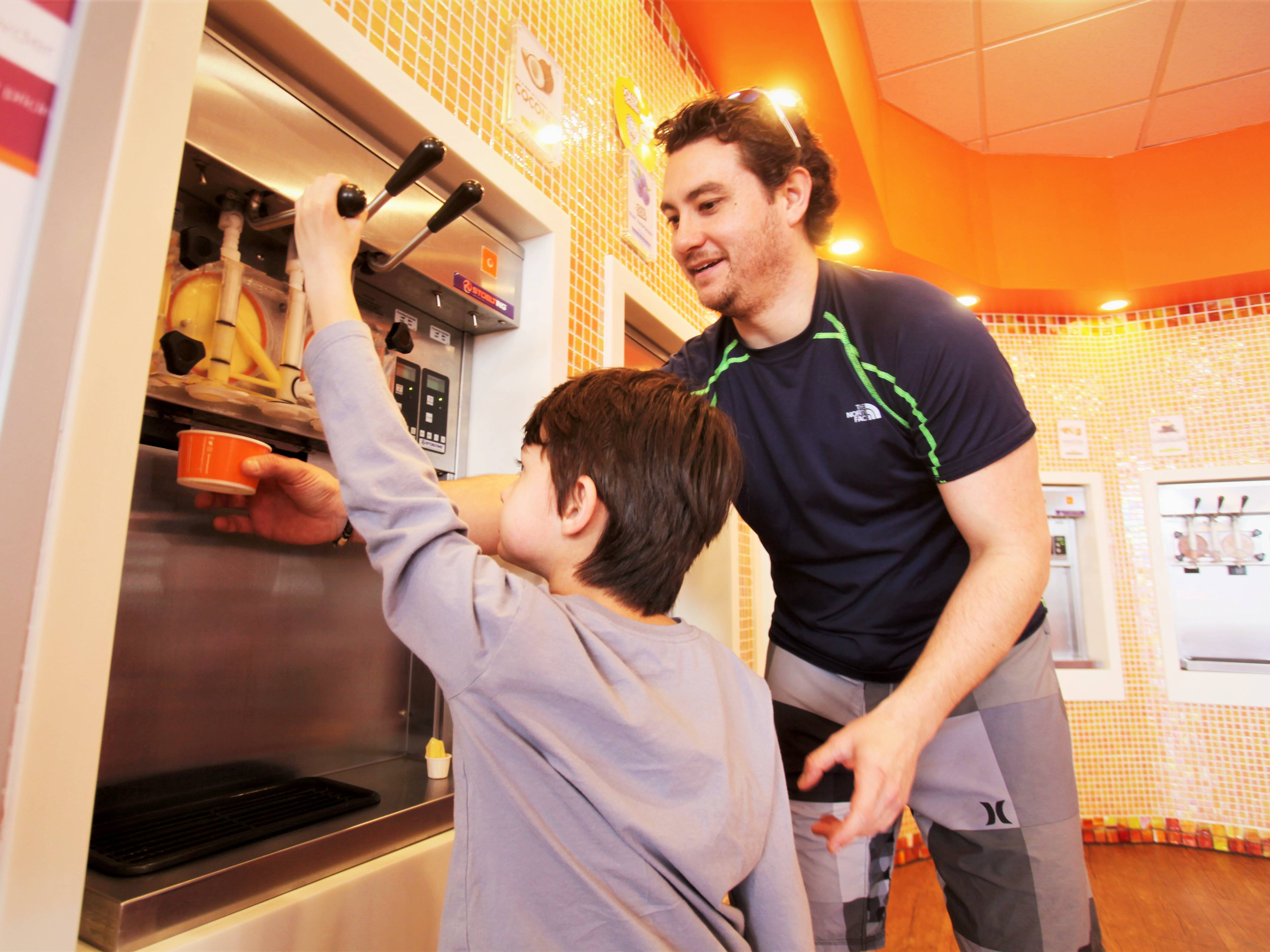 Five-year-old Kade Stenquist gets frozen yogurt with the help of his dad, David, at Orange Leaf in Springfield on March 14, 2019.