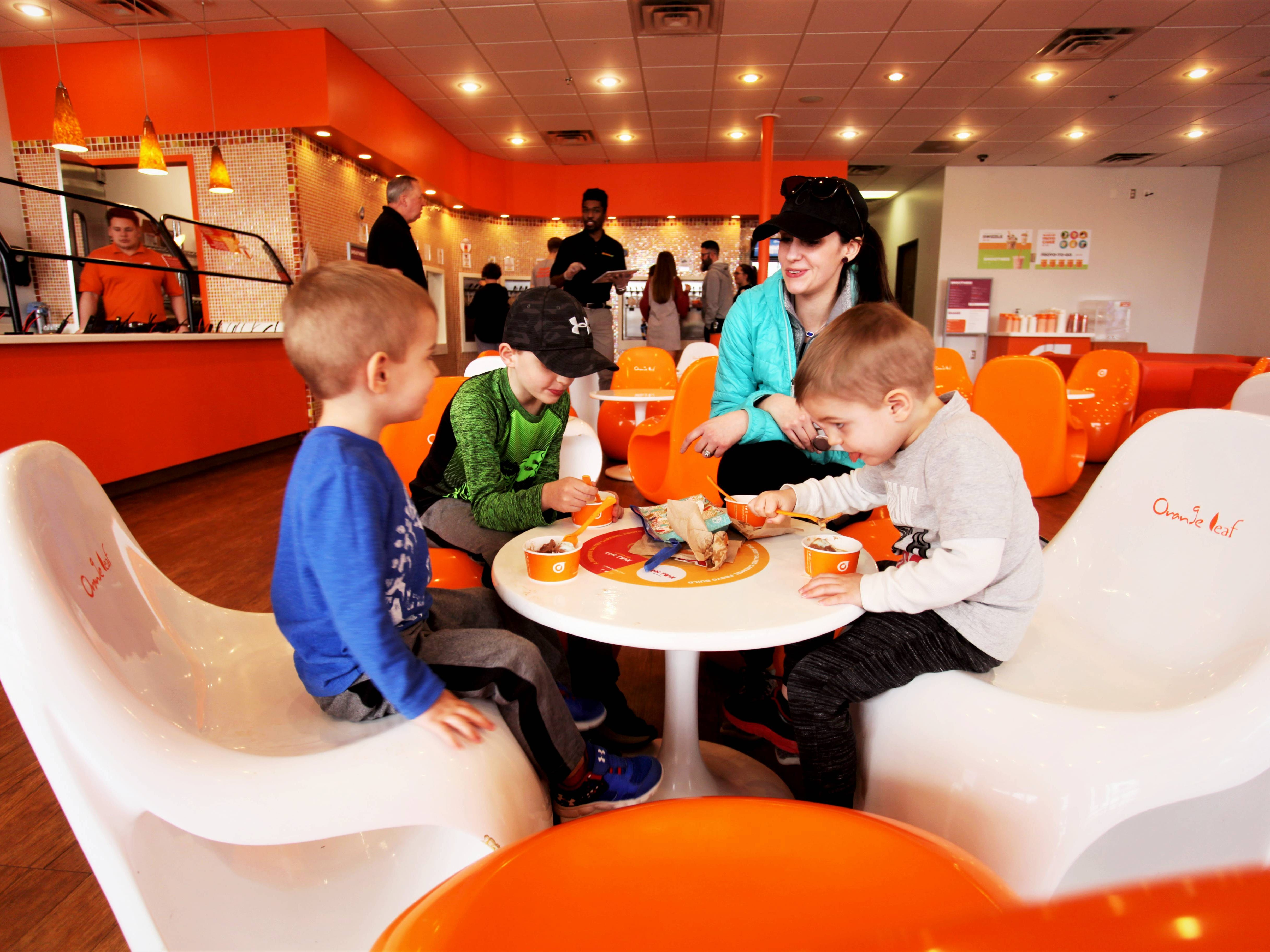 Two-year-old Elliot Colley, far left, eats frozen yogurt at Orange Leaf in Springfield with brothers Easton, 7, and Emerson, 4, while mother Rachel watches.