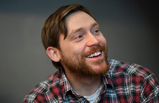 Adam Spaeth smiles while talking about his community-based art projects Wednesday, March 13,  in his St. Cloud studio.
