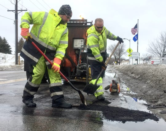 St. Cloud Public Works  employees Leroy Huling, left, and Jordan Proell repair a pothole Thursday, March 14 on Lincoln Avenue SE.