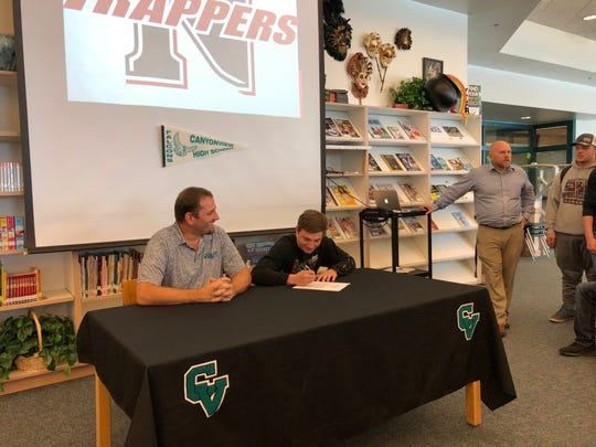 Brady Lowry (middle) signs a ceremonial NLI to Northwest College as his father, Dallas (left), and Canyon View's athletic director, Kyle Robinson (right), look on.