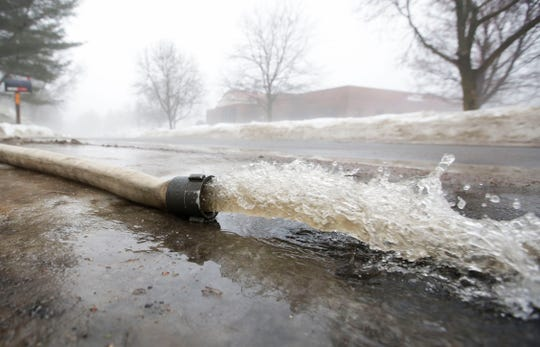 Water is pumped out near a storm drain on Indiana Avenue on Thursday, March 14, 2019, in Stevens Point, Wis. Warmer temperatures and recent rainfall has led to flooding throughout the area, and more rain and snow melt is expected in the coming days.