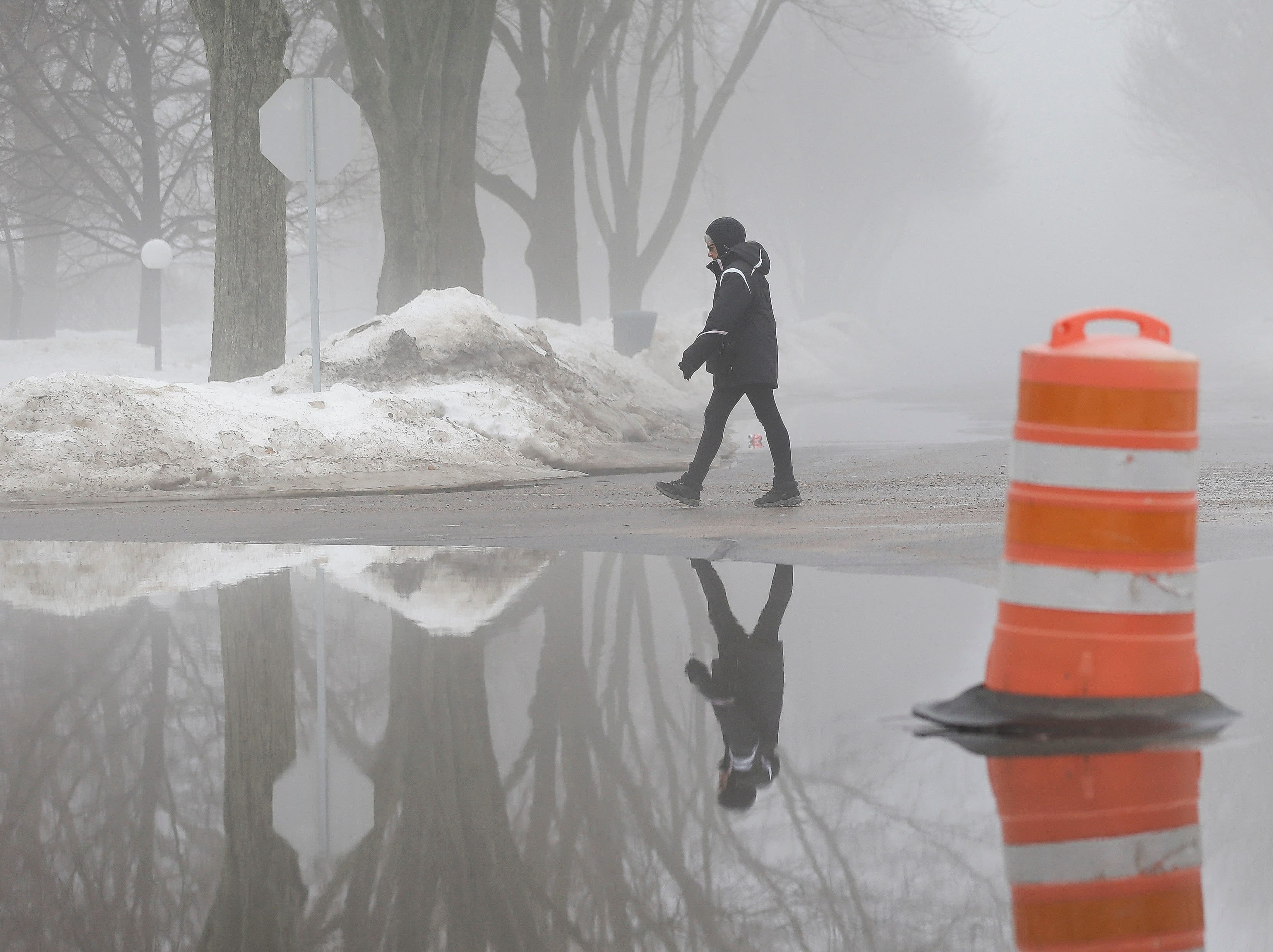 A woman crosses the flooded intersection of Indiana Avenue and Jordan Lane on Thursday, March 14, 2019, in Stevens Point, Wis. Warmer temperatures and recent rainfall has led to flooding throughout the area, and more rain and snow melt is expected in the coming days.