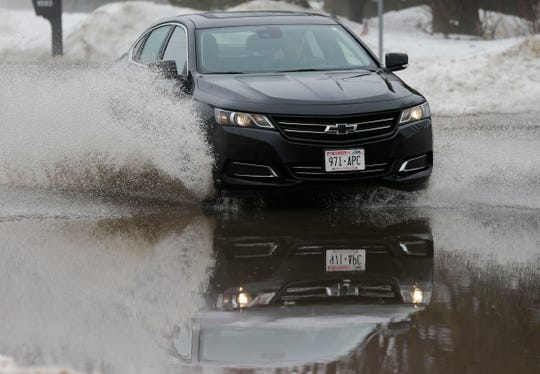 A car drives through floodwaters on Jordan Lane on Thursday, March 14, 2019, in Stevens Point, Wis. Warmer temperatures and recent rainfall has led to flooding throughout the area, and more rain and snow melt is expected in the coming days.