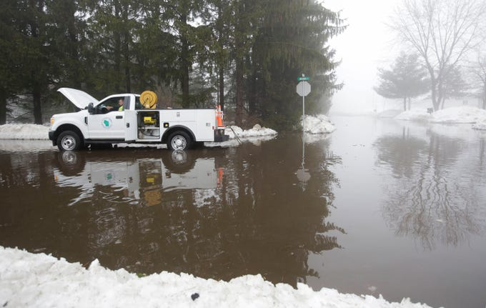 A Stevens Point Public Utilities worker pumps out floodwaters from the intersection of Indiana Avenue and Regent Street on Thursday, March 14, 2019, in Stevens Point, Wis. Warmer temperatures and recent rainfall has led to flooding throughout the area, and more rain and snow melt is expected in the coming days.