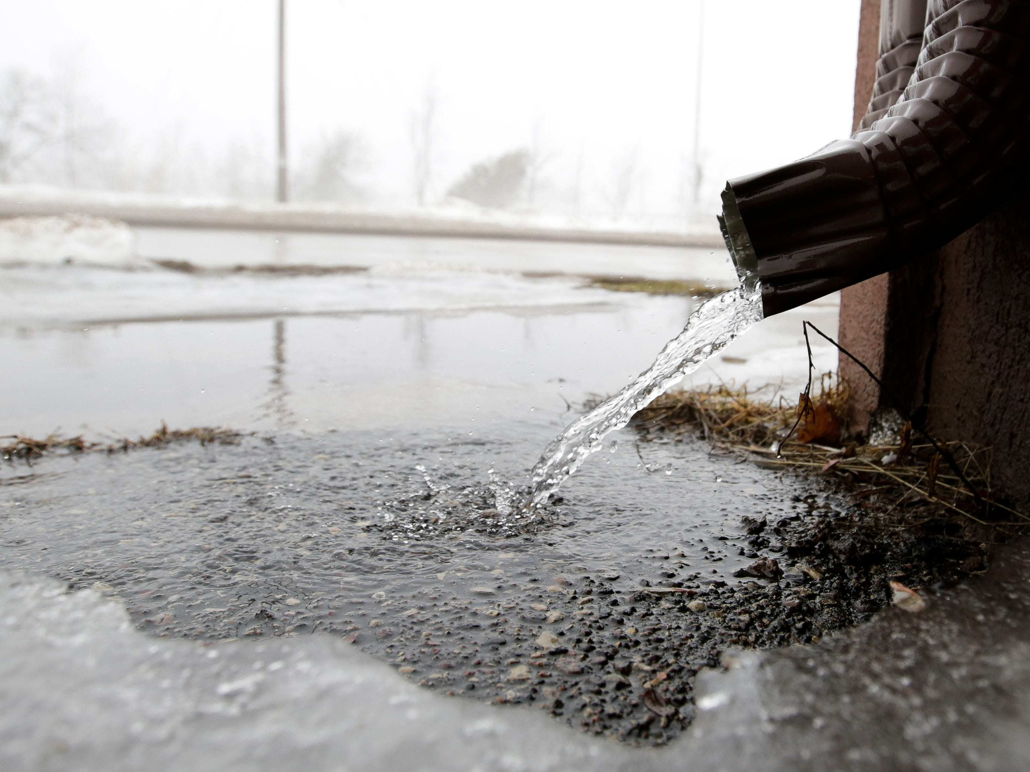 Water drains from a downspout on Thursday, March 14, 2019, in downtown Stevens Point, Wis. Warmer temperatures and recent rainfall has led to flooding throughout the area, and more rain and snow melt is expected in the coming days.