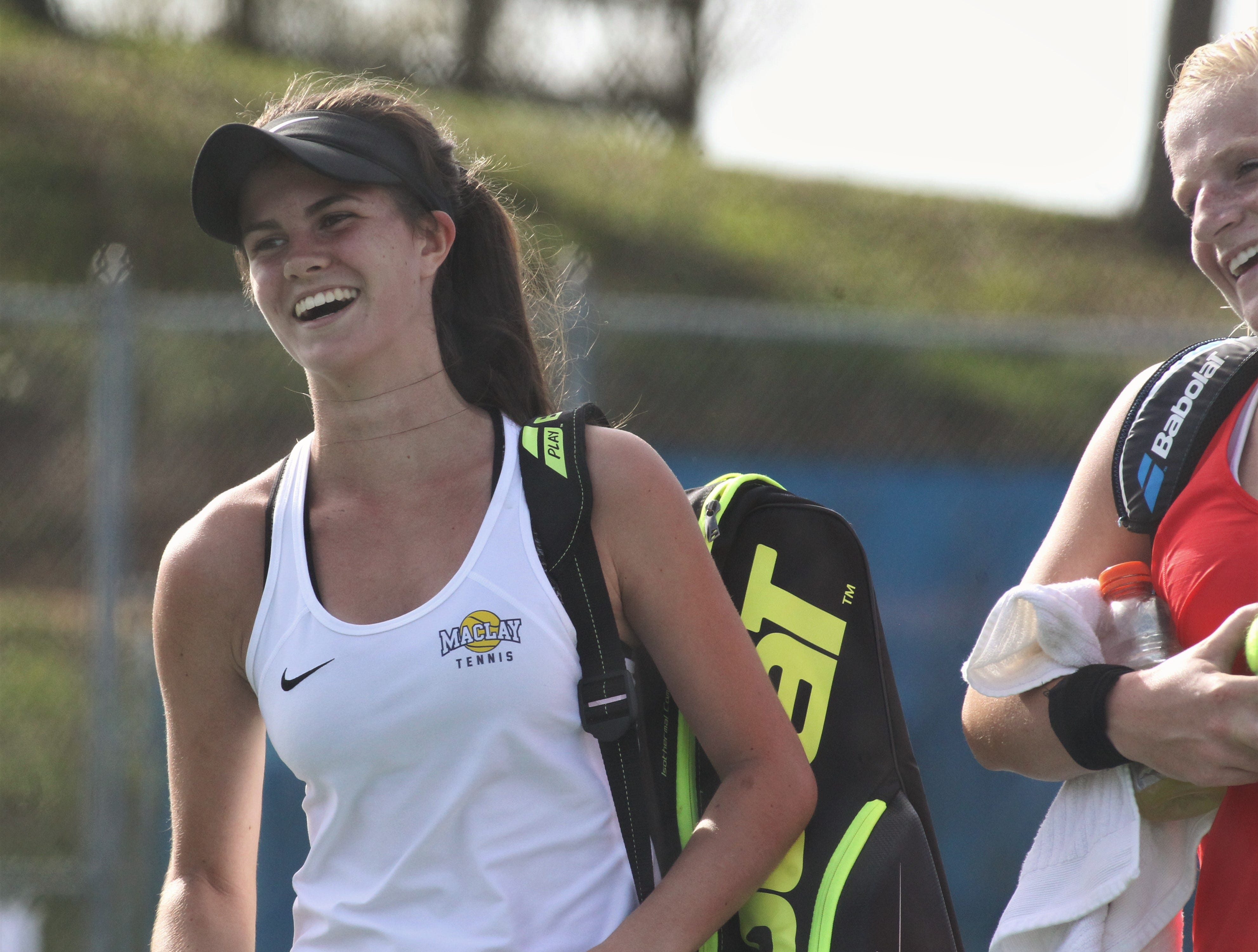 Maclay's Madison Perkins laughs with Leon's Jules Grady after they play during the boys and girls tennis city tournament at Tom Brown Park on March 13, 2019.