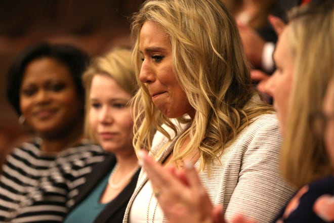Angela Drzewiecki, widow of Air Force Staff Sgt. Carl Enis who died in a helicopter crash in Western Iraq, fights back tears as she and her late husband are recognized at the opening of the Florida Senate session Thursday, March 14, 2019.