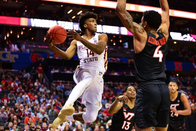Florida State senior forward Terrance Mann, 14, looks for an open man on the court during the second half of the ACC Quarterfinal game in Charlotte on Thursday.