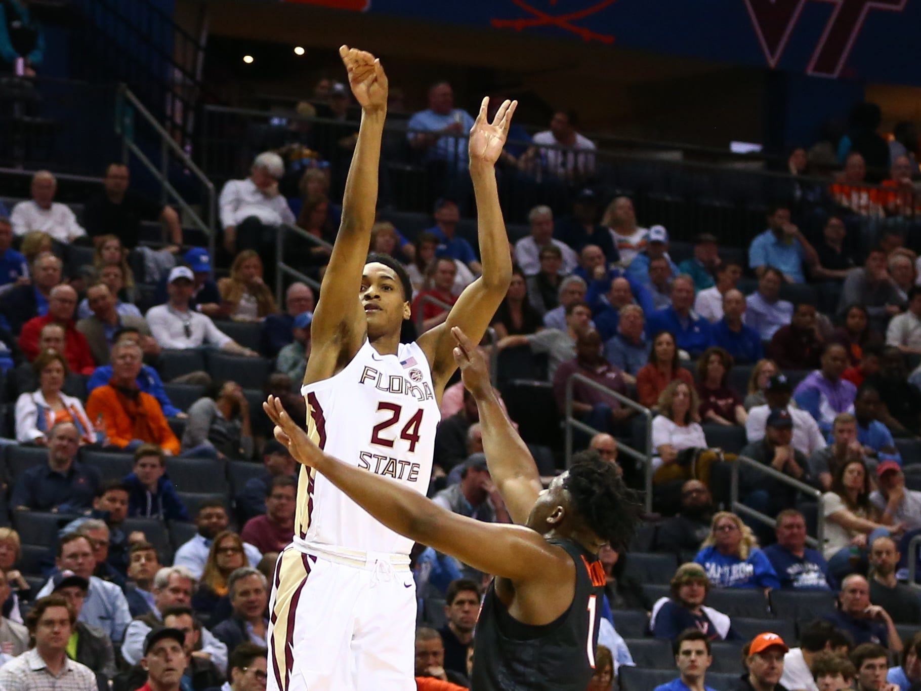 Mar 14, 2019; Charlotte, NC, USA; Florida State Seminoles guard Devin Vassell (24) shoots a three-point basket against Virginia Tech Hokies guard Isaiah Wilkins (1) in the first half in the ACC conference tournament at Spectrum Center. Mandatory Credit: Jeremy Brevard-USA TODAY Sports