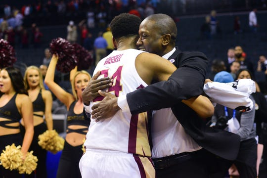 Florida State assistant coach Dennis Gates embraces freshman forward Devin Vassell after Florida State's 65-63 overtime victory over Virginia Tech in Charlotte on Thursday.